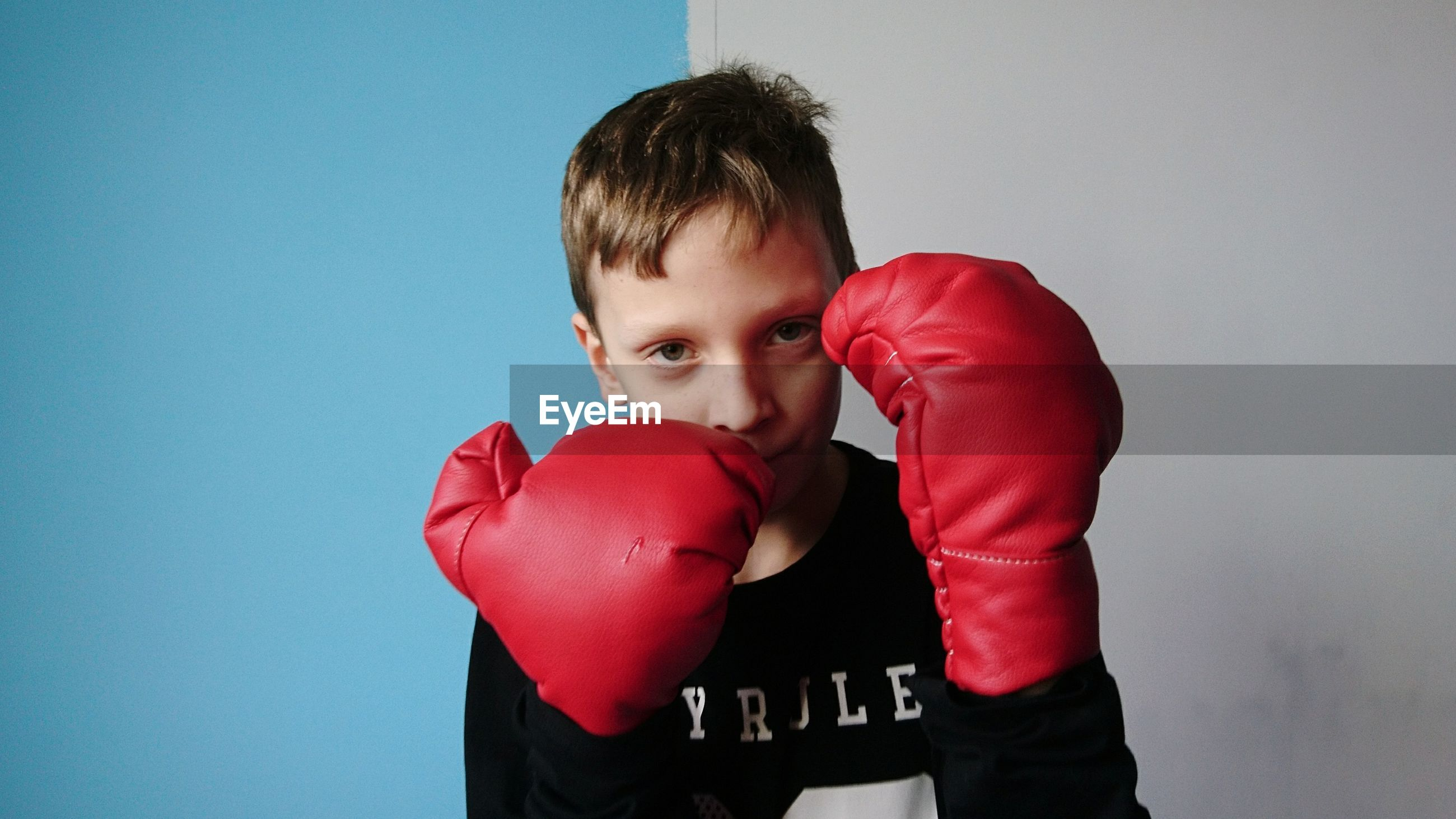 Portrait of confident boy with boxing gloves standing against wall