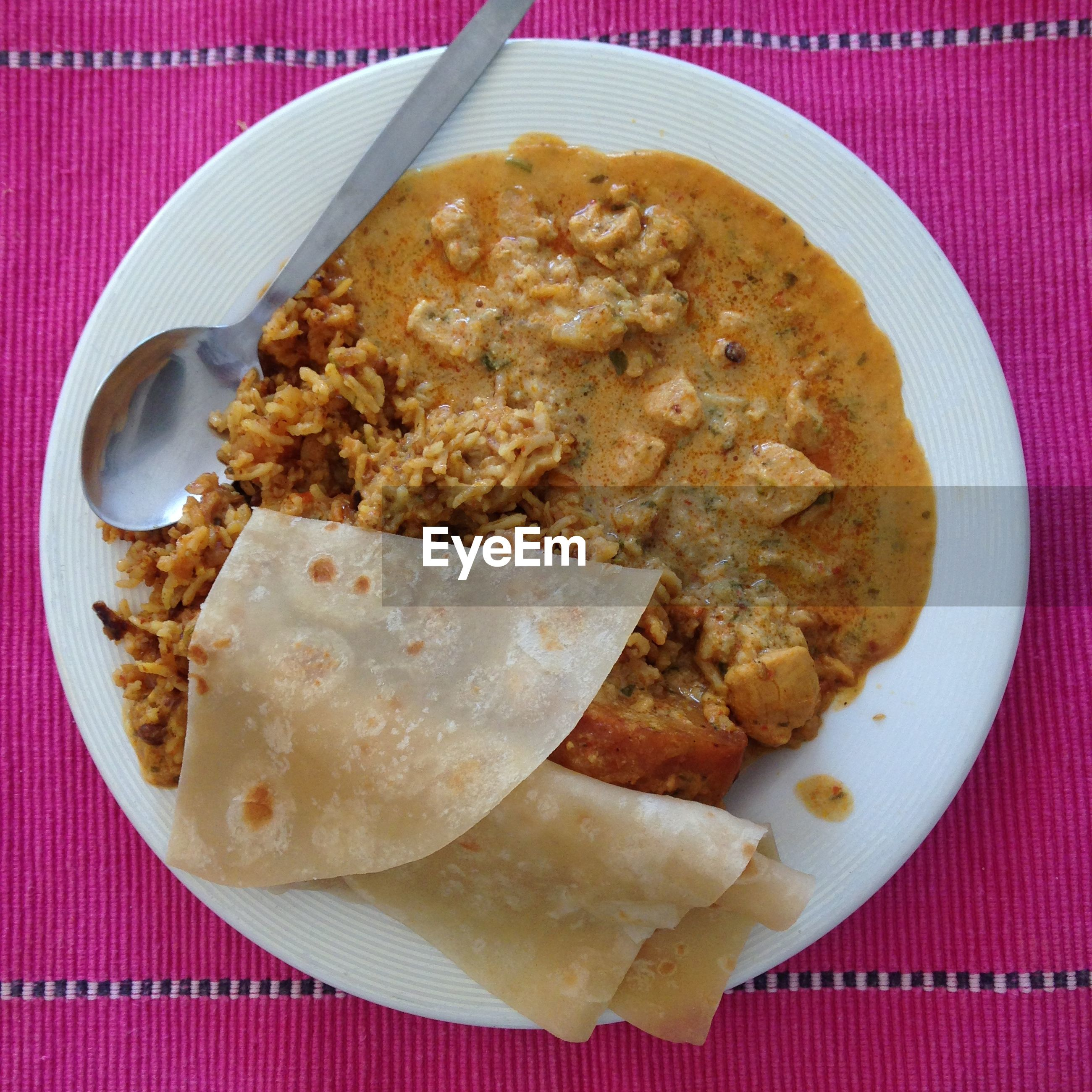 High angle view of rice and curry with chapattis served on plate