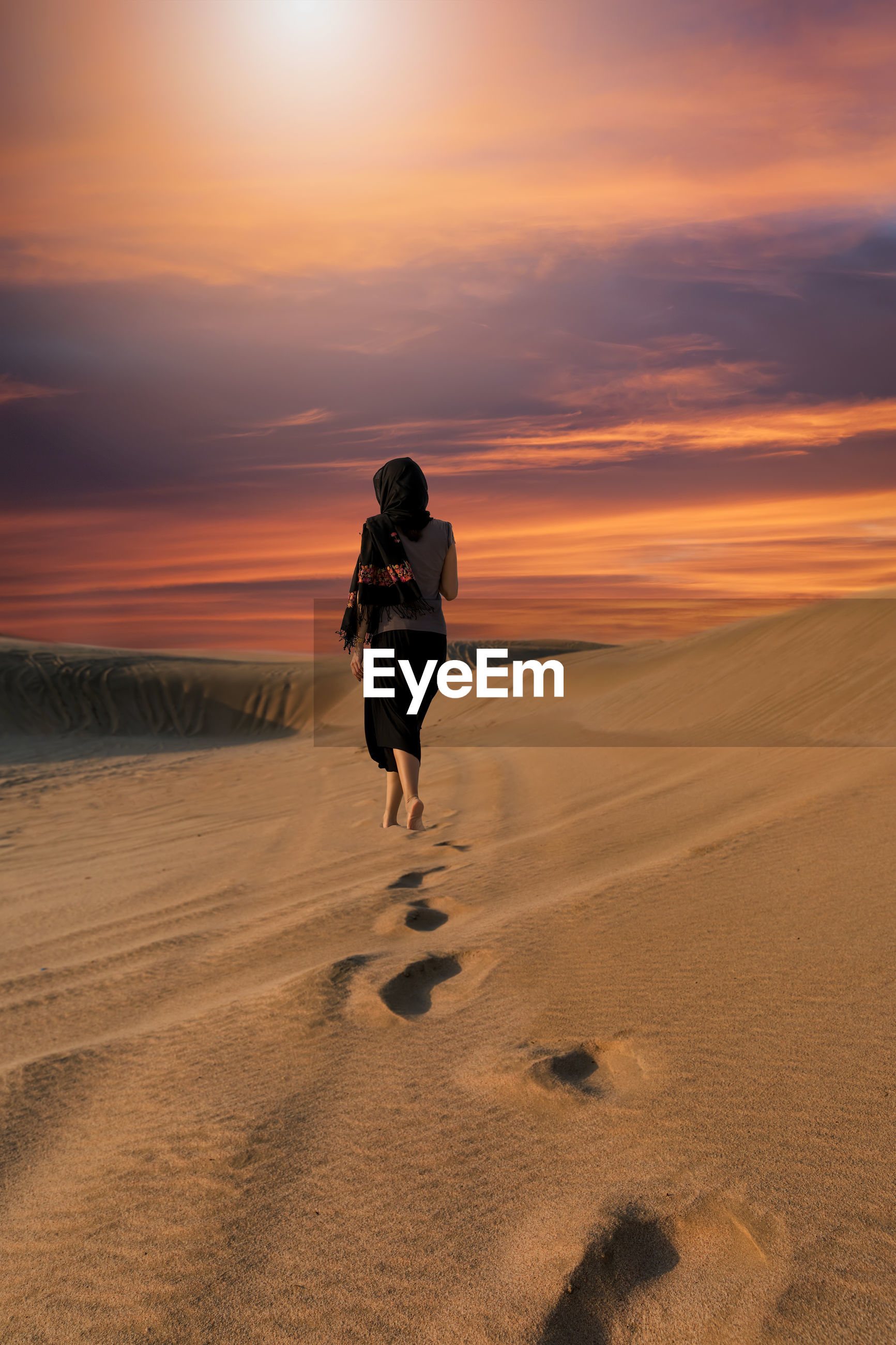 Rear view of woman in desert during sunset