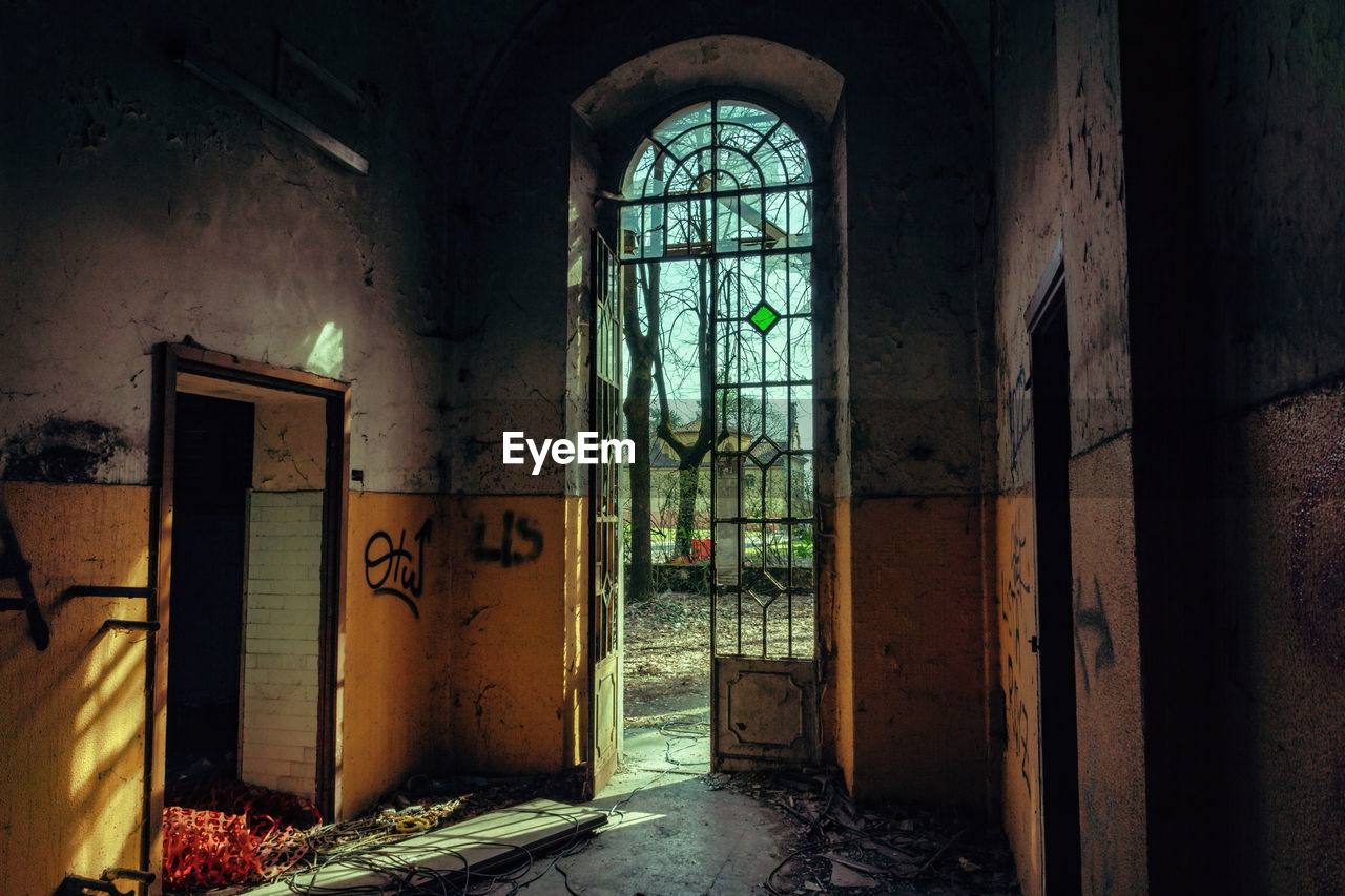 architecture, indoors, entrance, door, building, abandoned, window, no people, built structure, arch, day, run-down, damaged, absence, old, empty, house, obsolete, bad condition, decline, deterioration, messy, ruined