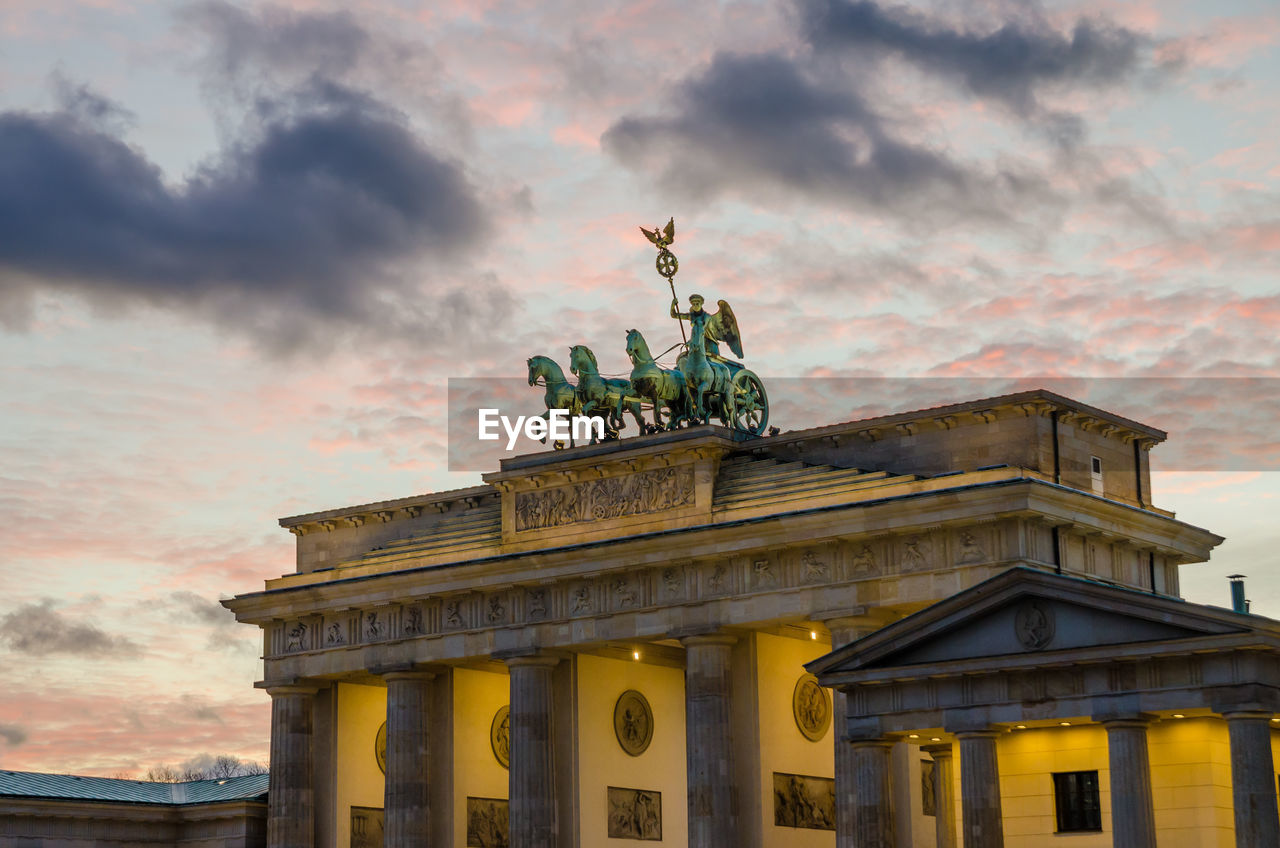 Low angle view of illuminated brandenburg gate against cloudy sky during twilight, berlin, germany