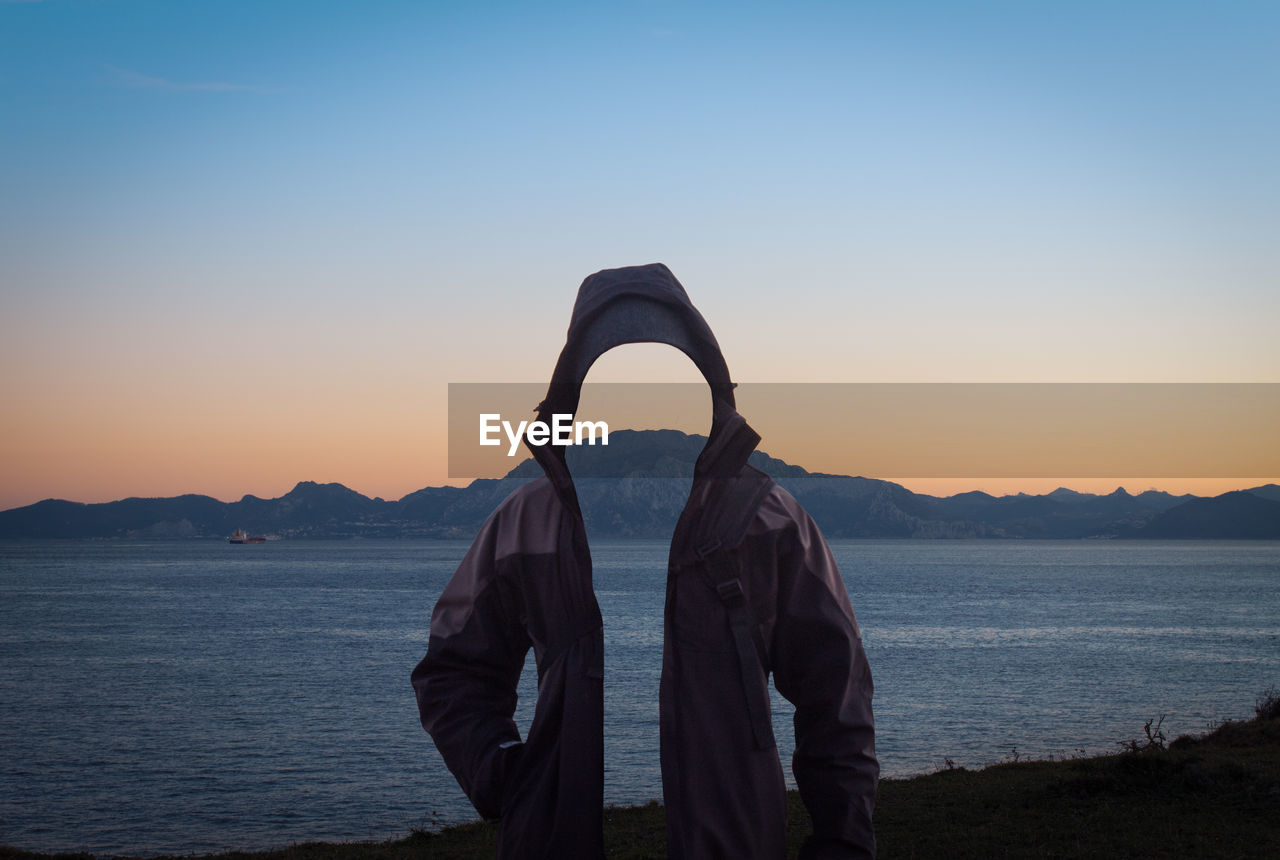 Digital composite image of invisible person wearing hooded jacket while standing by sea against clear sky during sunset