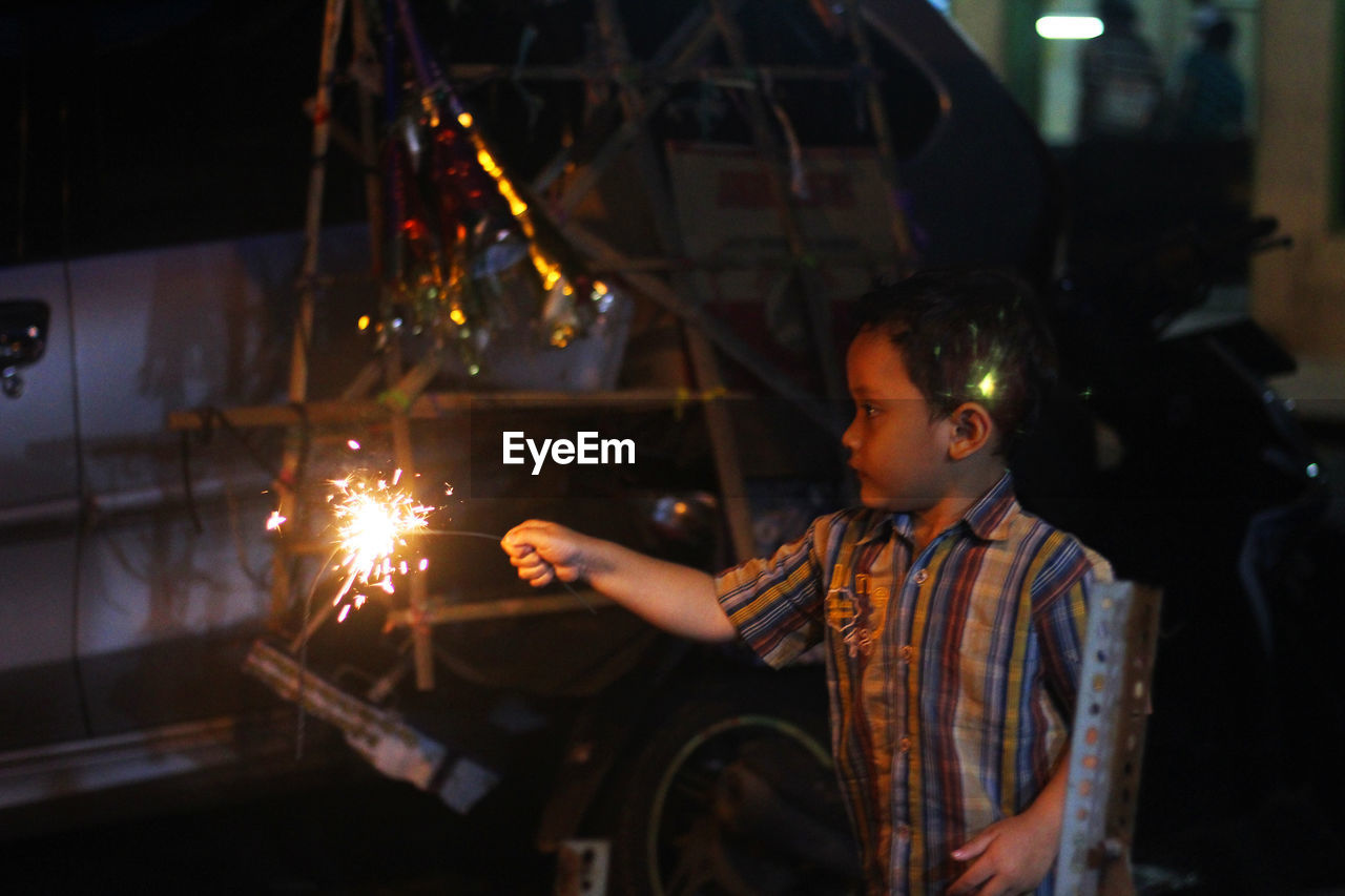 child, childhood, one person, illuminated, boys, males, real people, men, glowing, night, motion, lifestyles, leisure activity, waist up, standing, three quarter length, casual clothing, looking, burning, sparkler, innocence