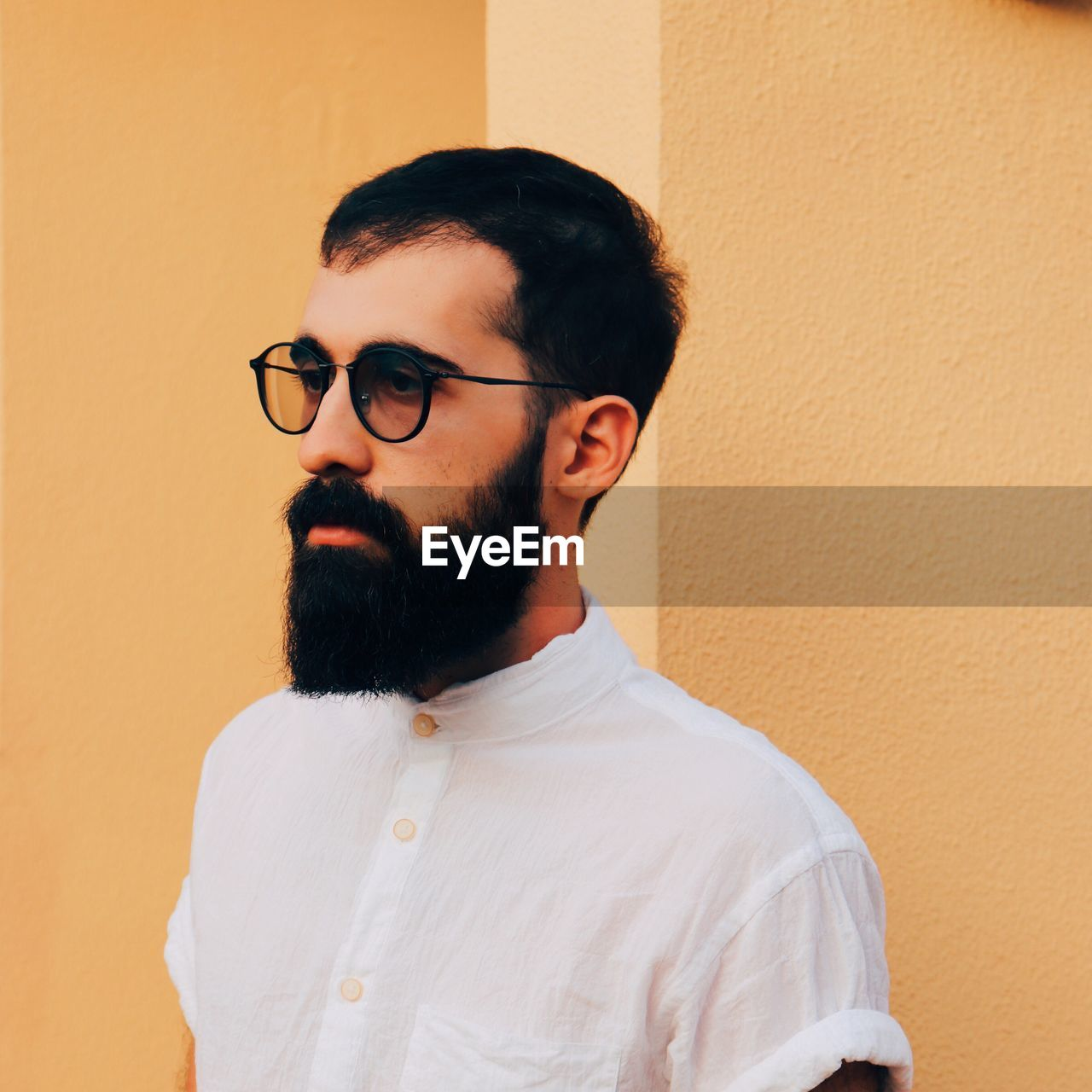 Close-up of man in sunglasses against wall