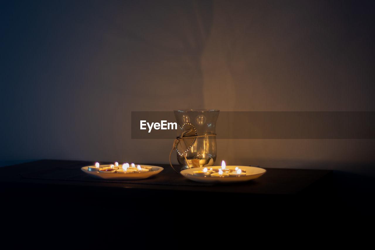 CLOSE-UP OF ILLUMINATED TEA LIGHT CANDLE ON TABLE