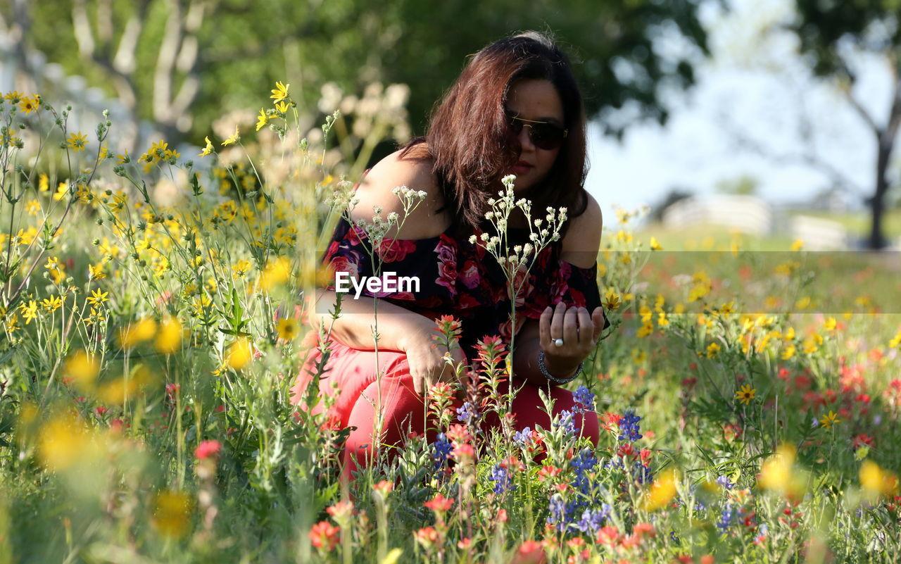 Portrait Of Woman In Sunglasses Amidst Flowering Plants