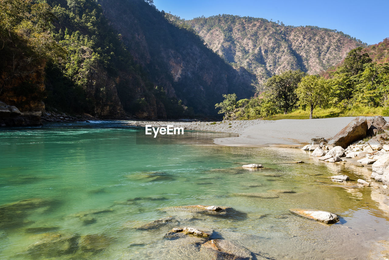 water, mountain, beauty in nature, scenics - nature, rock, tree, tranquility, day, nature, solid, tranquil scene, rock - object, non-urban scene, no people, plant, land, sea, mountain range, idyllic, outdoors, flowing water, shallow, flowing