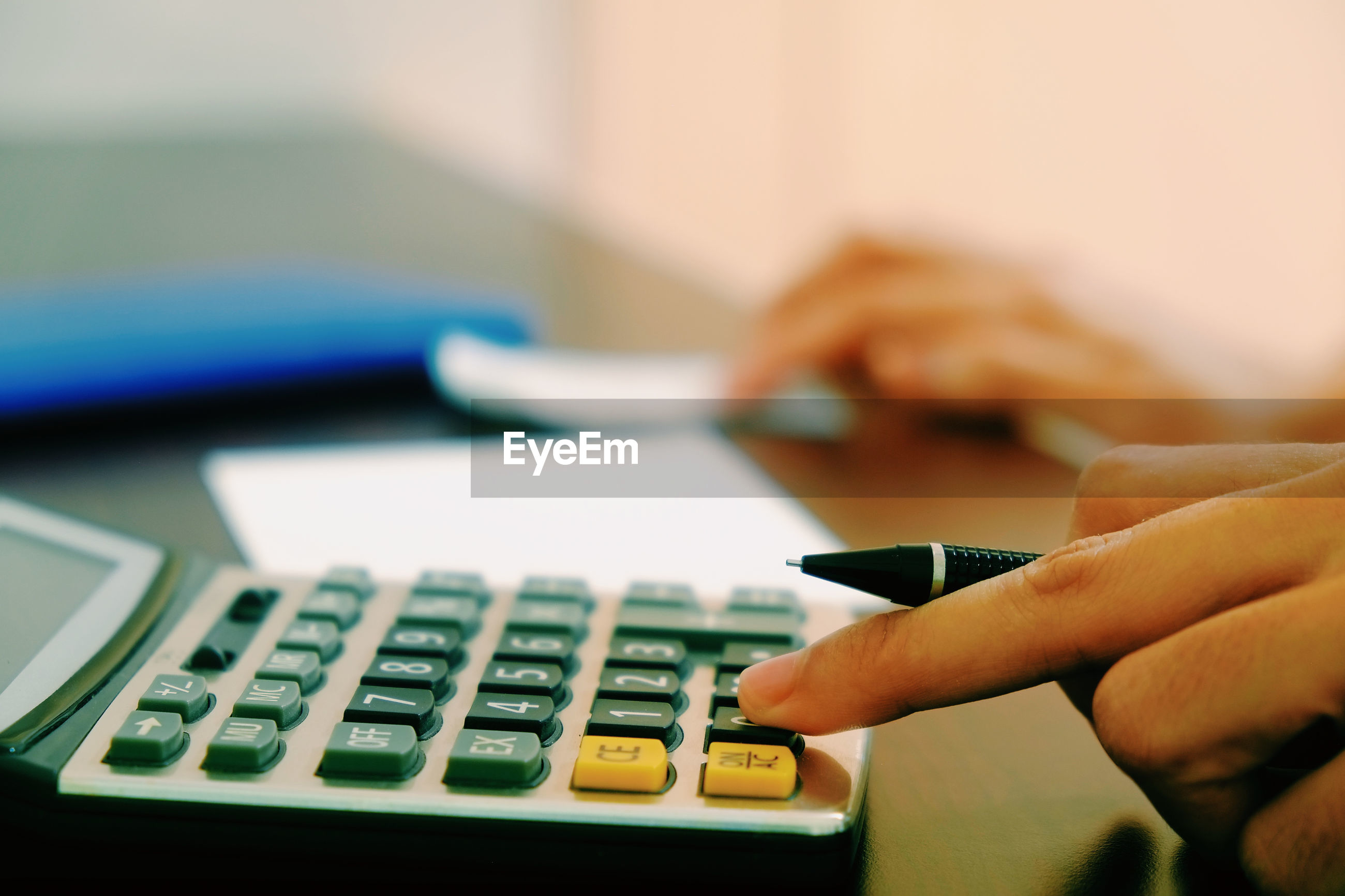 Close-up of hand using calculator on table