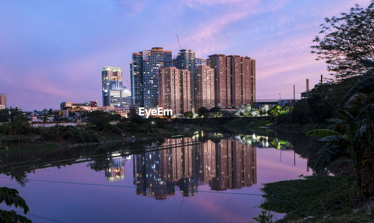 building exterior, architecture, built structure, reflection, water, sky, city, building, waterfront, tree, nature, no people, plant, cityscape, cloud - sky, modern, office building exterior, illuminated, skyscraper, outdoors, canal, purple, apartment, financial district