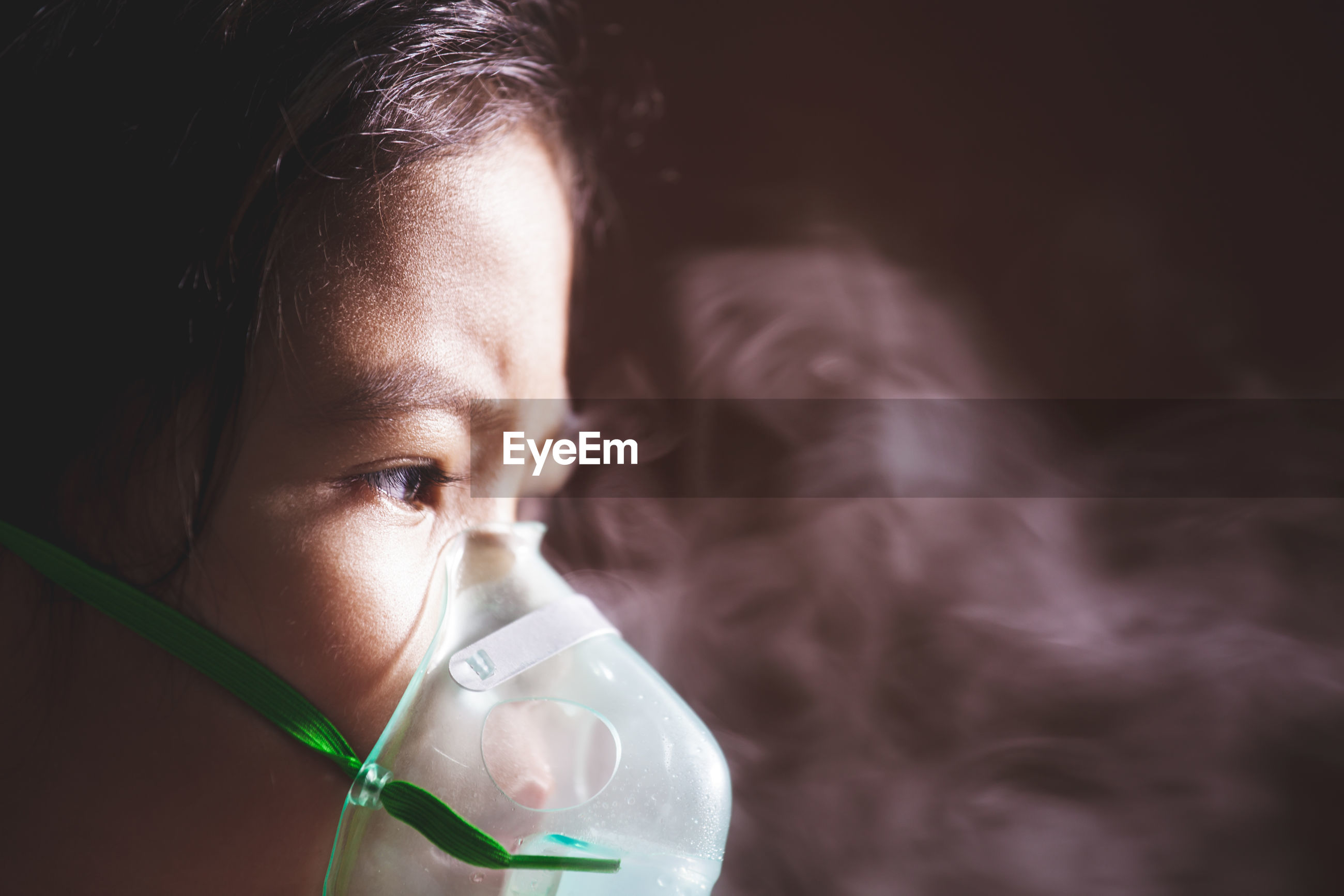 Close-up of girl wearing oxygen mask
