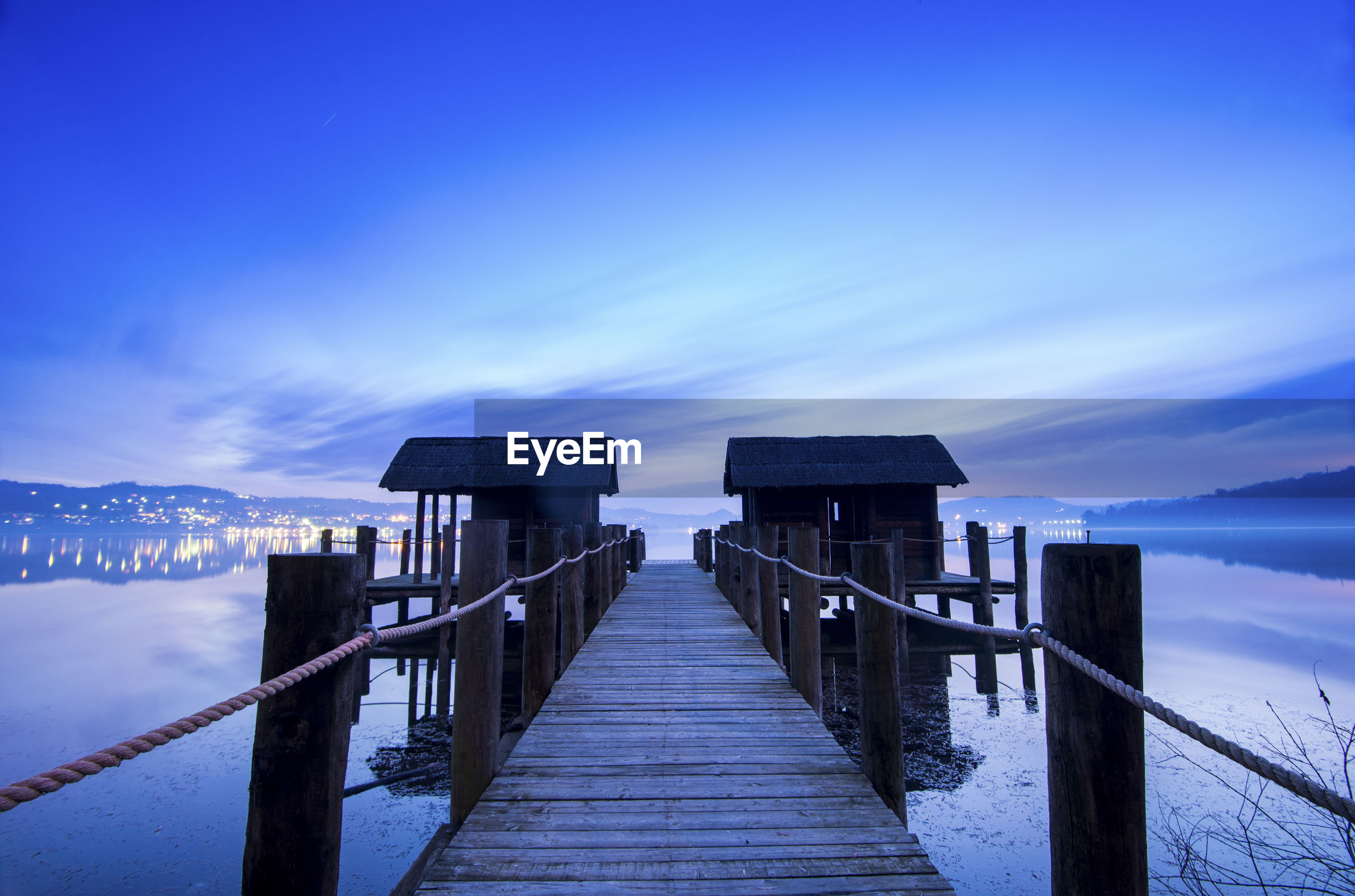 Wooden pier over lake against dramatic sky at dusk