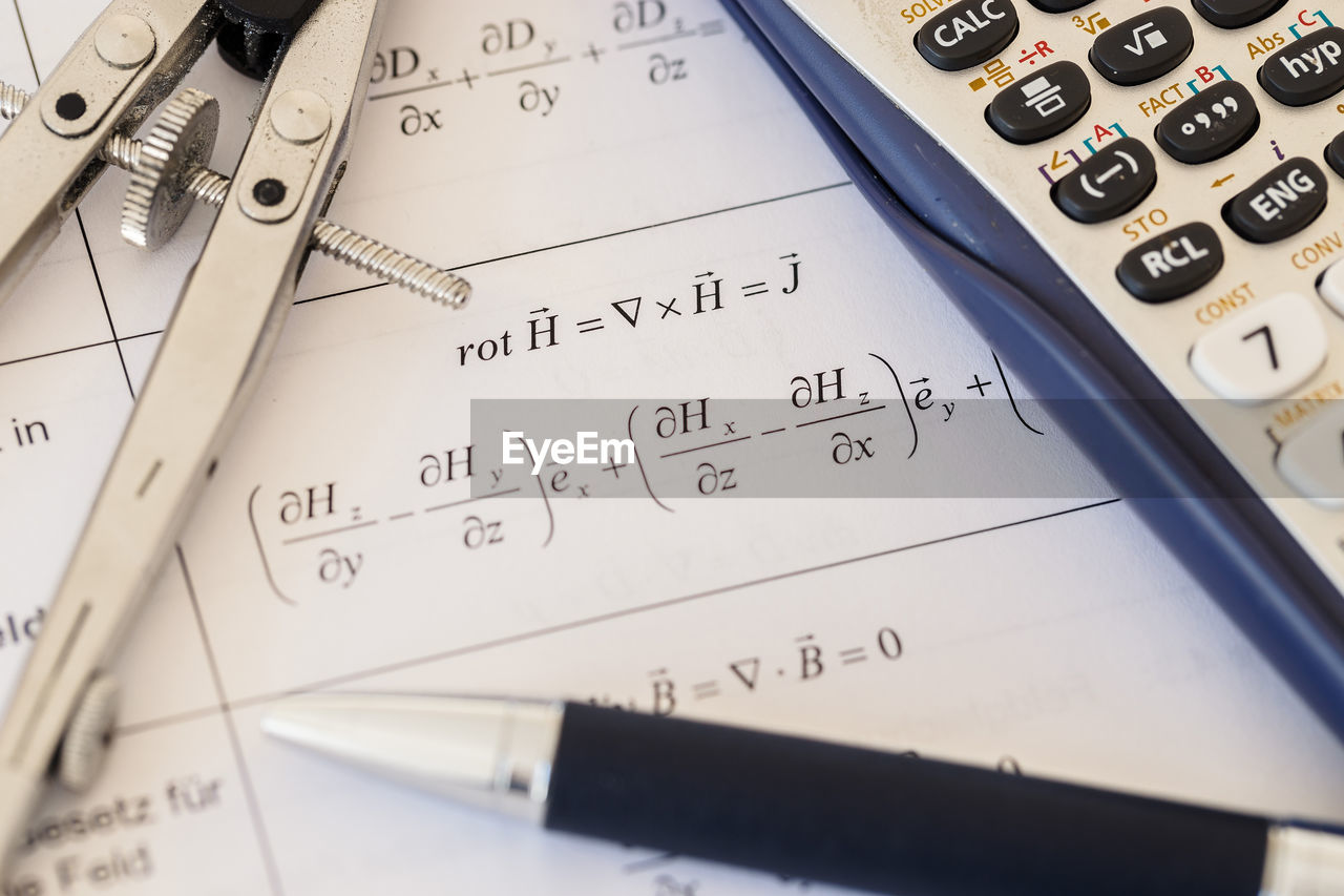 Close-up of text on paper with pen and calculator