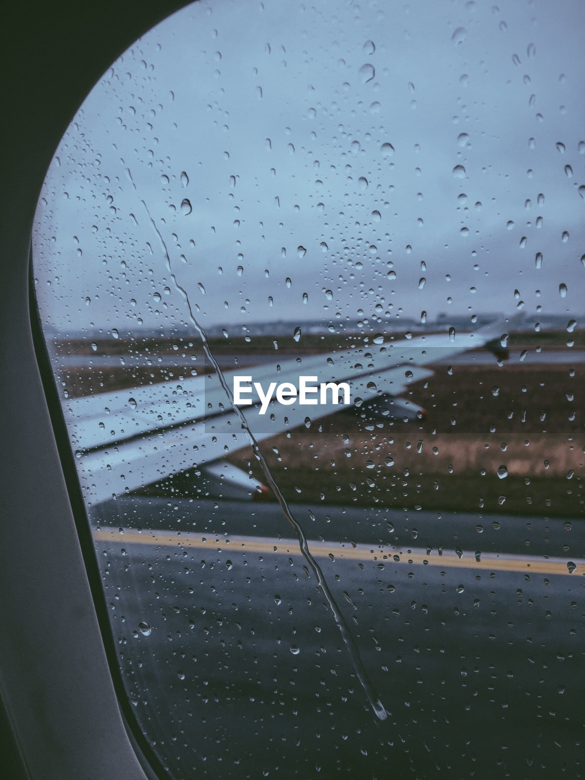 CLOSE-UP OF WATERDROPS ON GLASS WINDOW WITH VIEW OF AIRPLANE