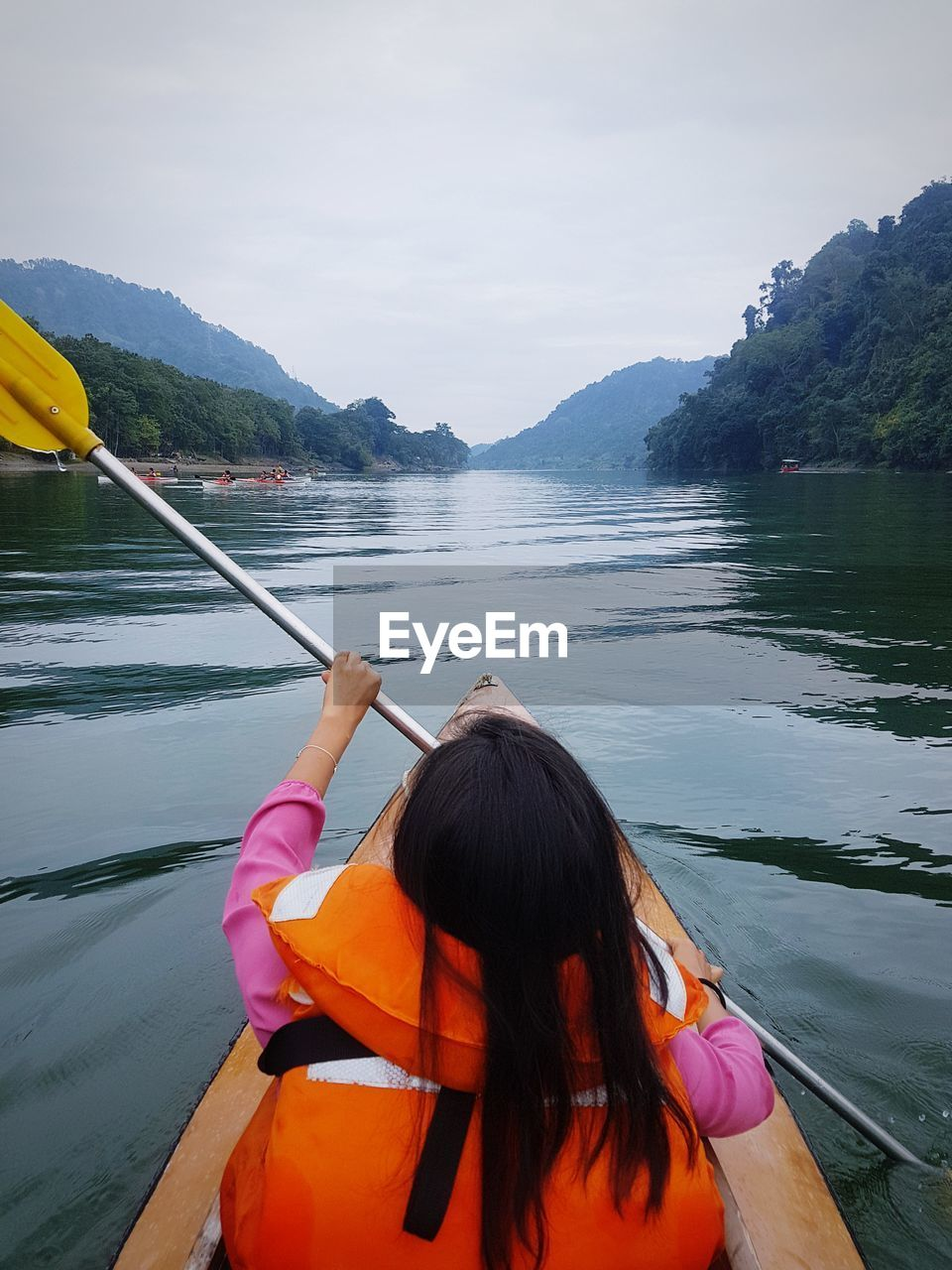 Rear View Of Woman Kayaking In Lake Against Sky