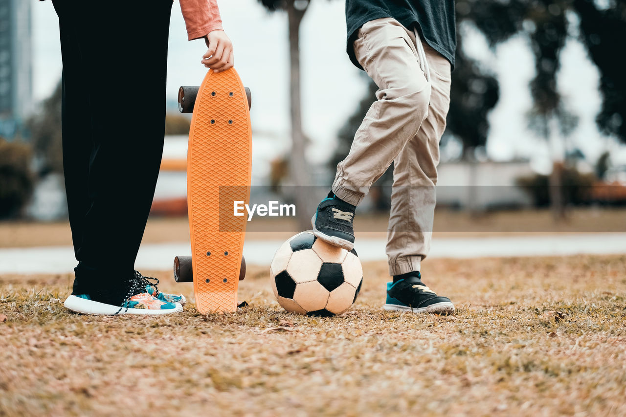 Low Section Of Friends With Skateboard And Soccer Ball On Field