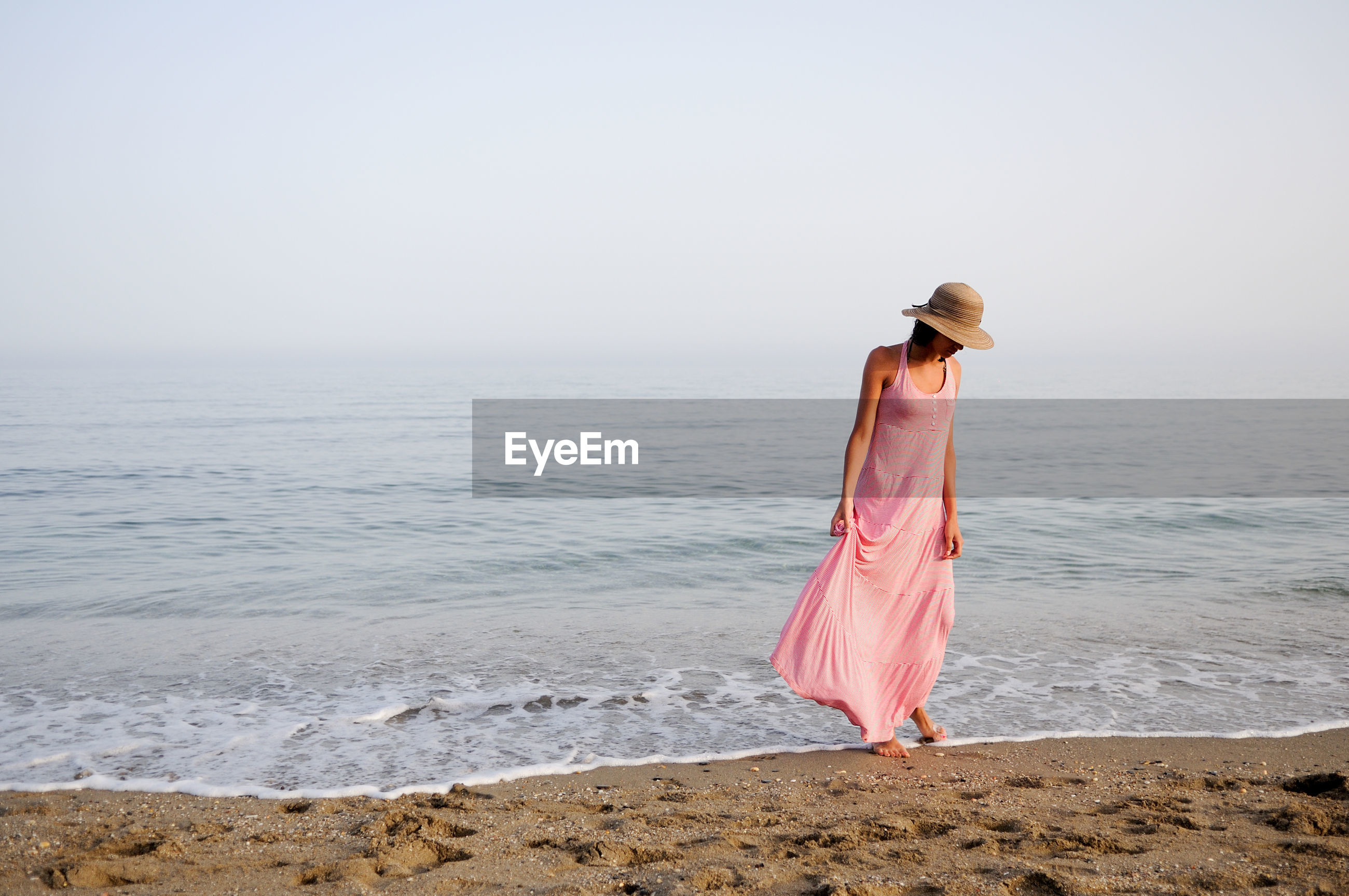Woman standing on shore at beach against sky