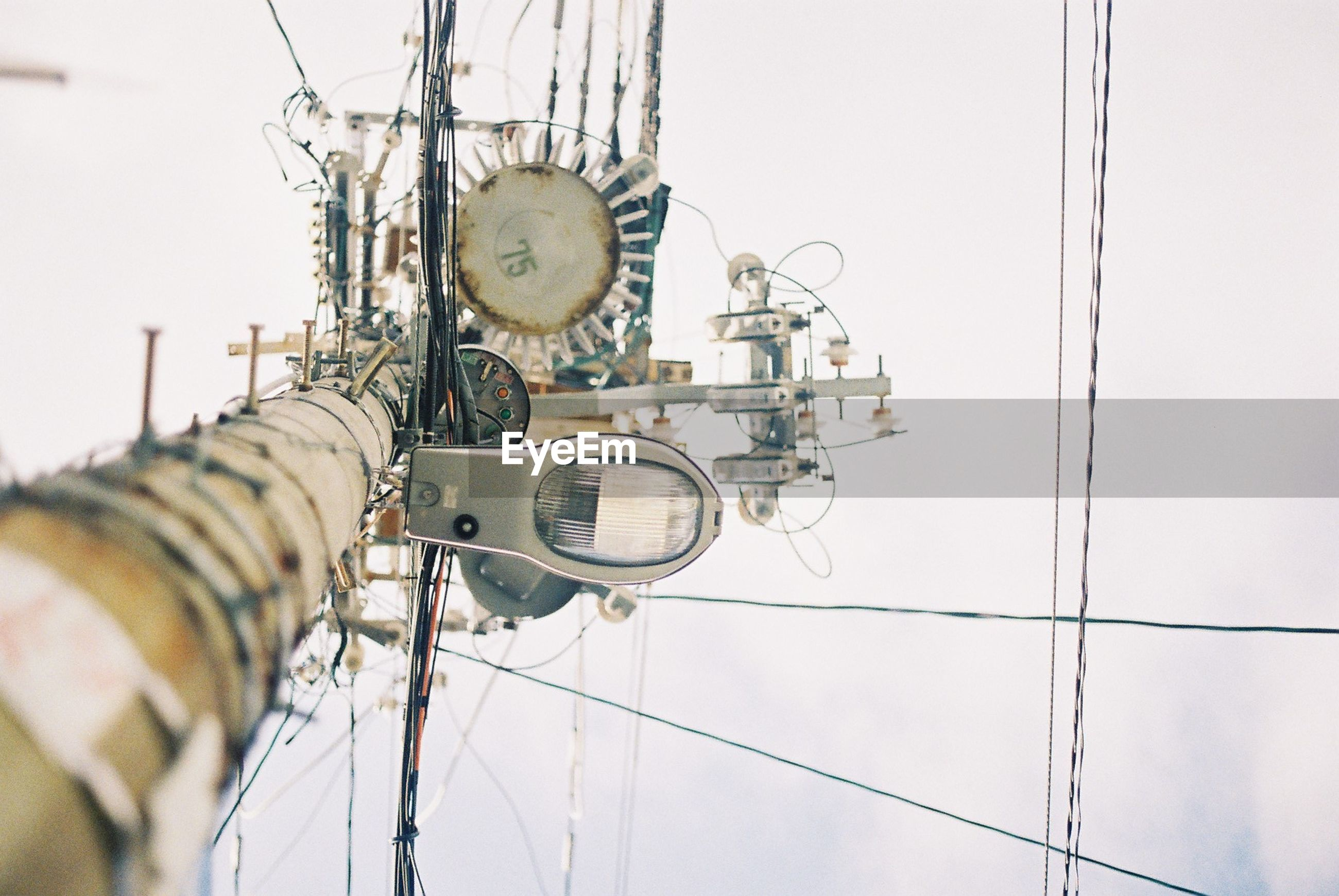 Directly below view of street light with complex electricity cables against sky