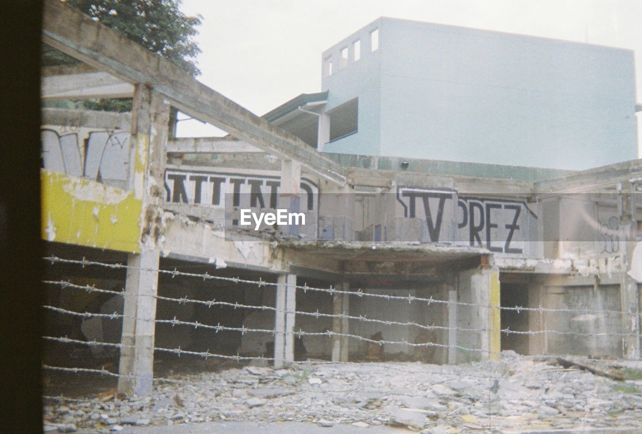 architecture, built structure, building exterior, day, no people, text, building, sky, nature, outdoors, communication, abandoned, wall, western script, construction industry, graffiti, industry, city, sign, old