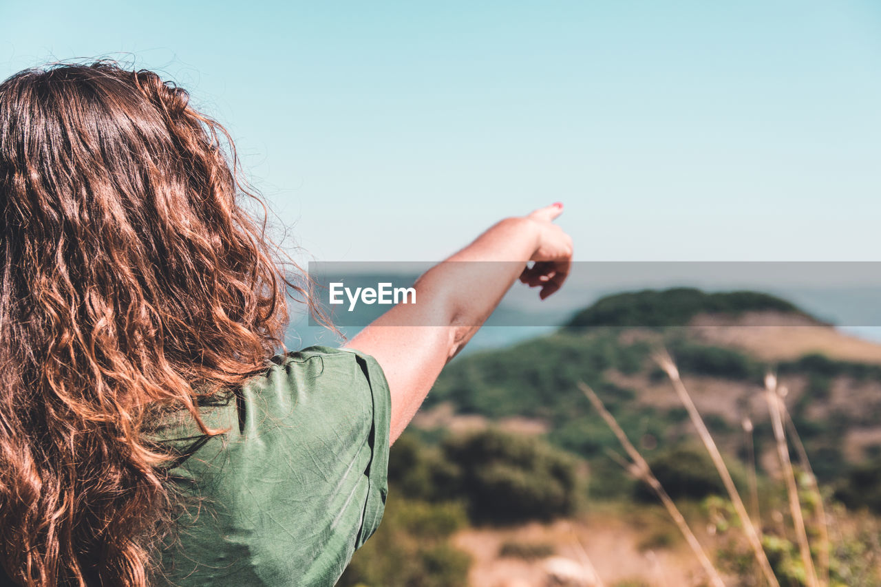 one person, rear view, real people, leisure activity, lifestyles, sky, nature, focus on foreground, hair, hairstyle, brown hair, adult, headshot, women, land, day, casual clothing, long hair, clear sky, outdoors, human arm