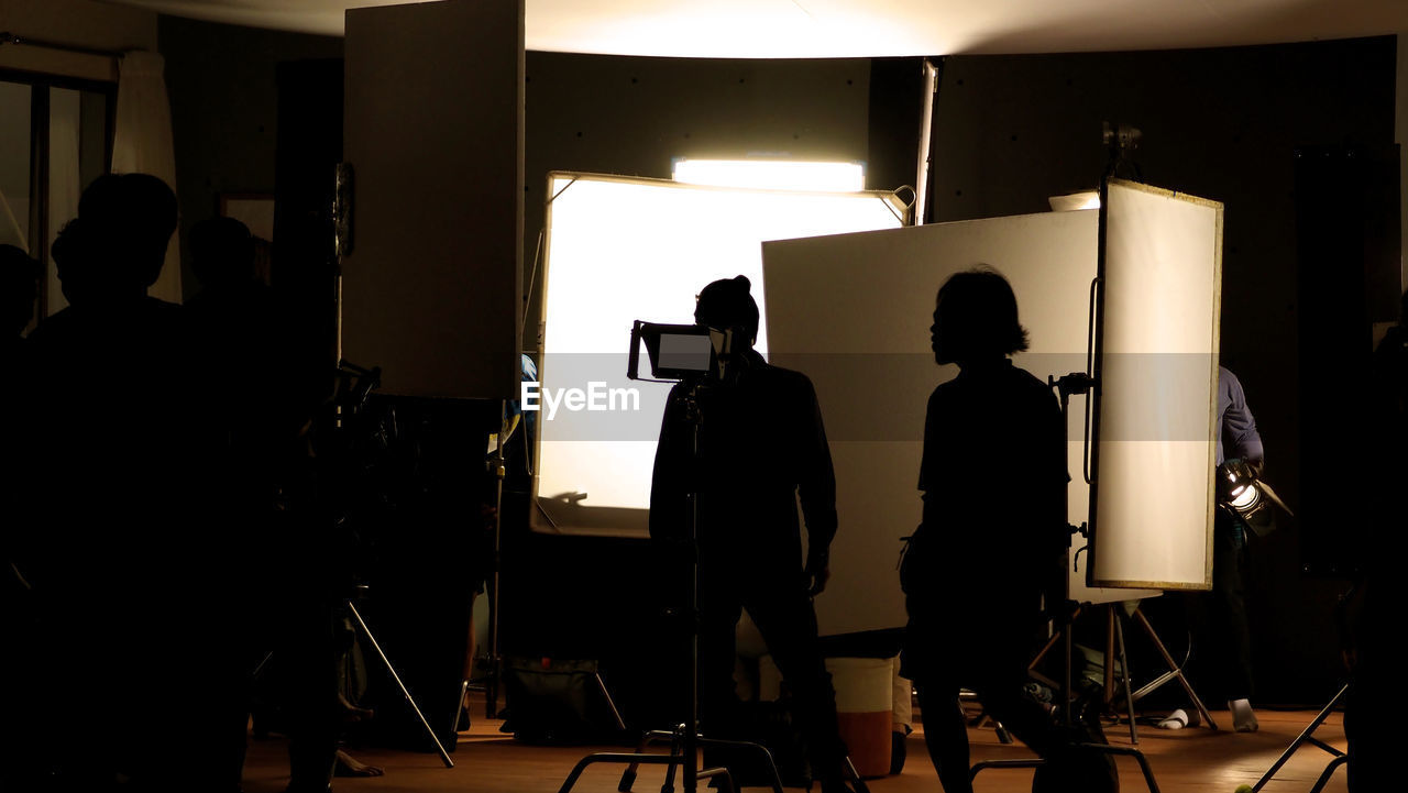men, real people, indoors, occupation, lighting equipment, arts culture and entertainment, studio, technology, film studio, people, illuminated, silhouette, group of people, photography themes, standing, working, music, photographic equipment, behind the scenes, filming, photo shoot, stage