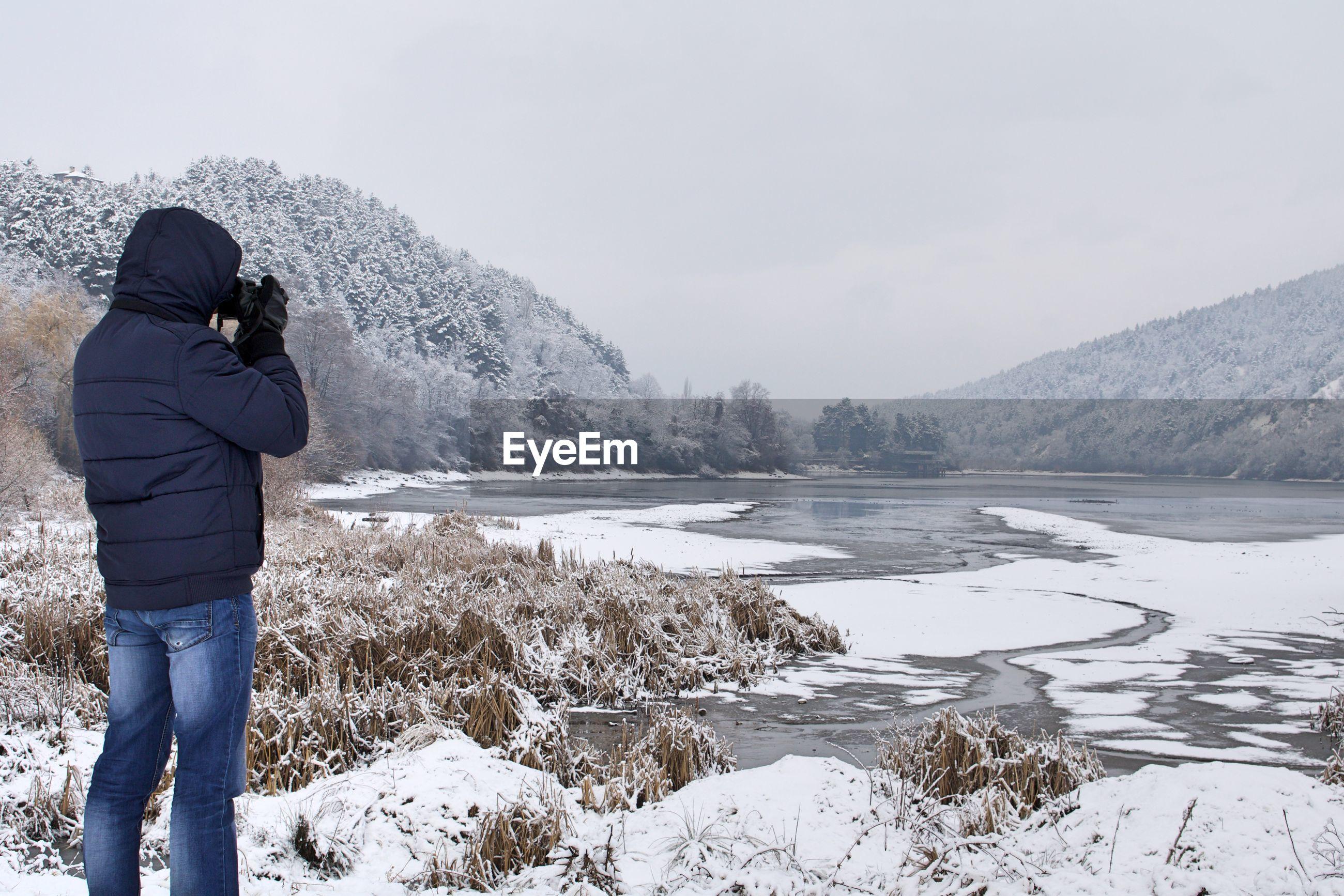 Man photographing frozen lake