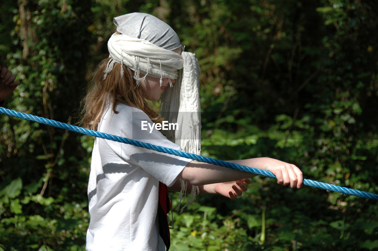 Side view of blindfolded girl walking while holding rope at park