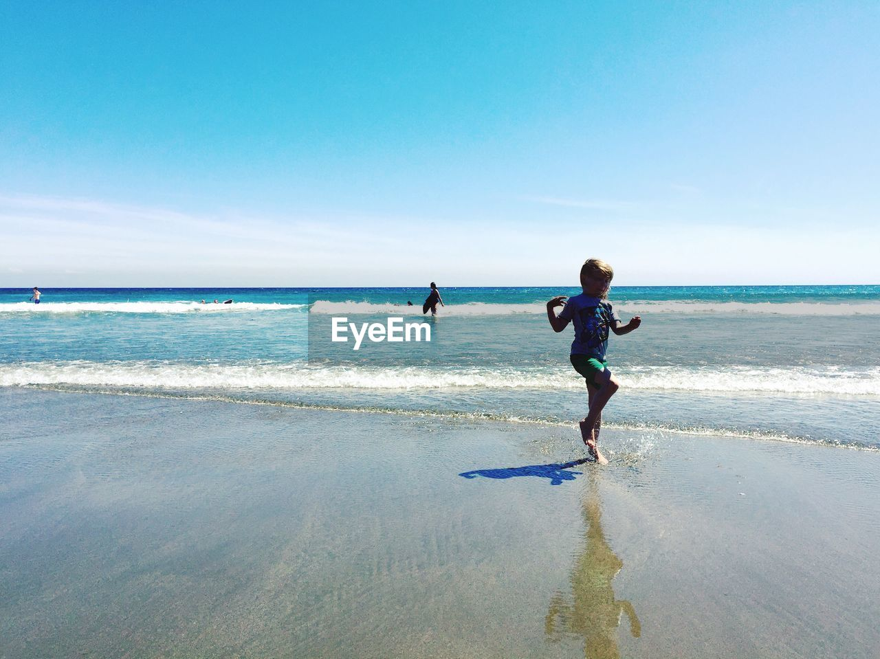 Girl playing on seashore at beach against clear sky