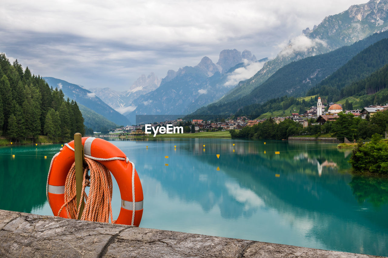 Life Belt Hanging By Lake By Mountains Against Sky