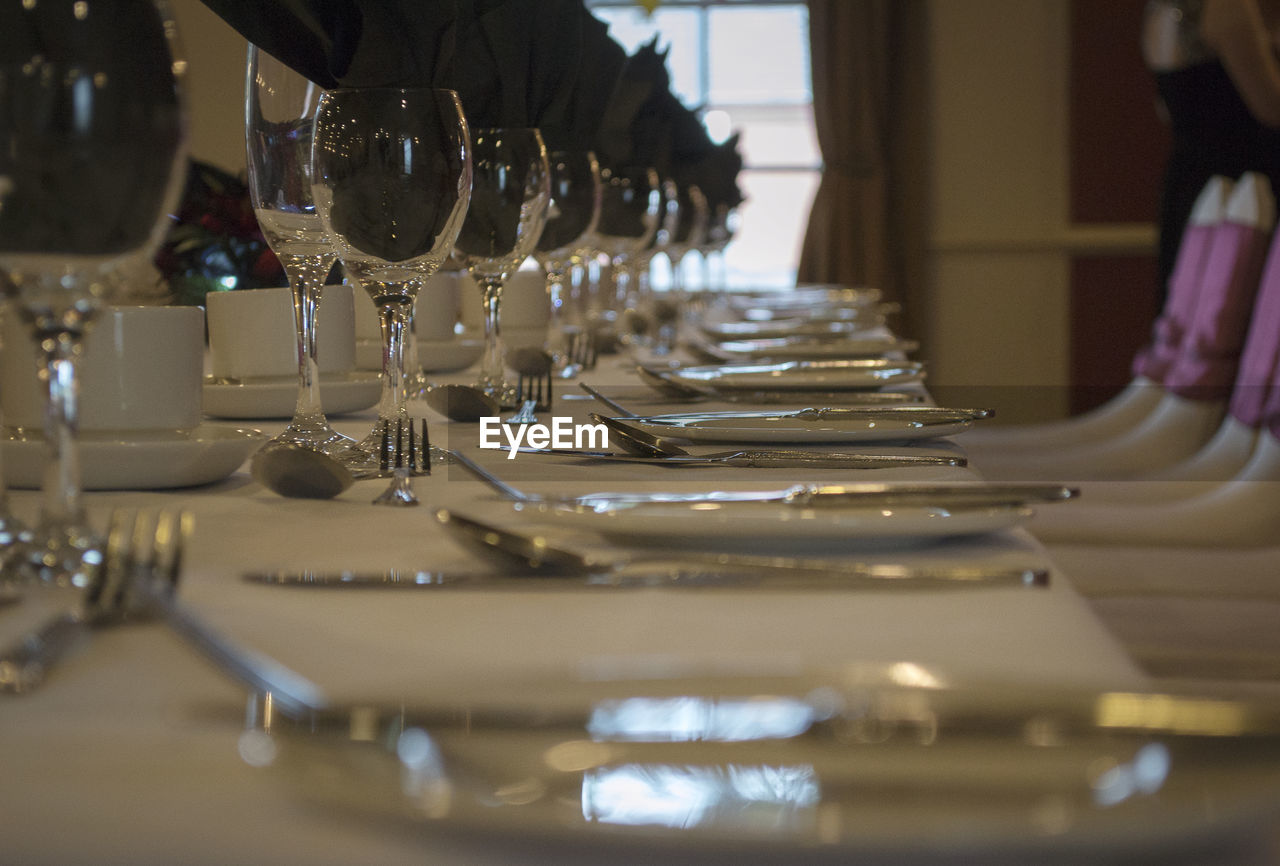 in a row, indoors, food and drink, selective focus, repetition, drink, arrangement, large group of objects, no people, order, refreshment, table, business, glass, close-up, empty, wineglass, freshness, setting