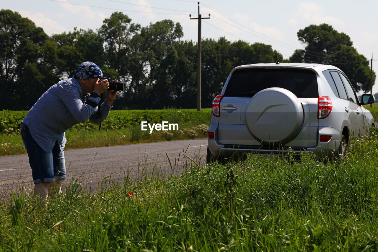 Man photographing by grassy field on road