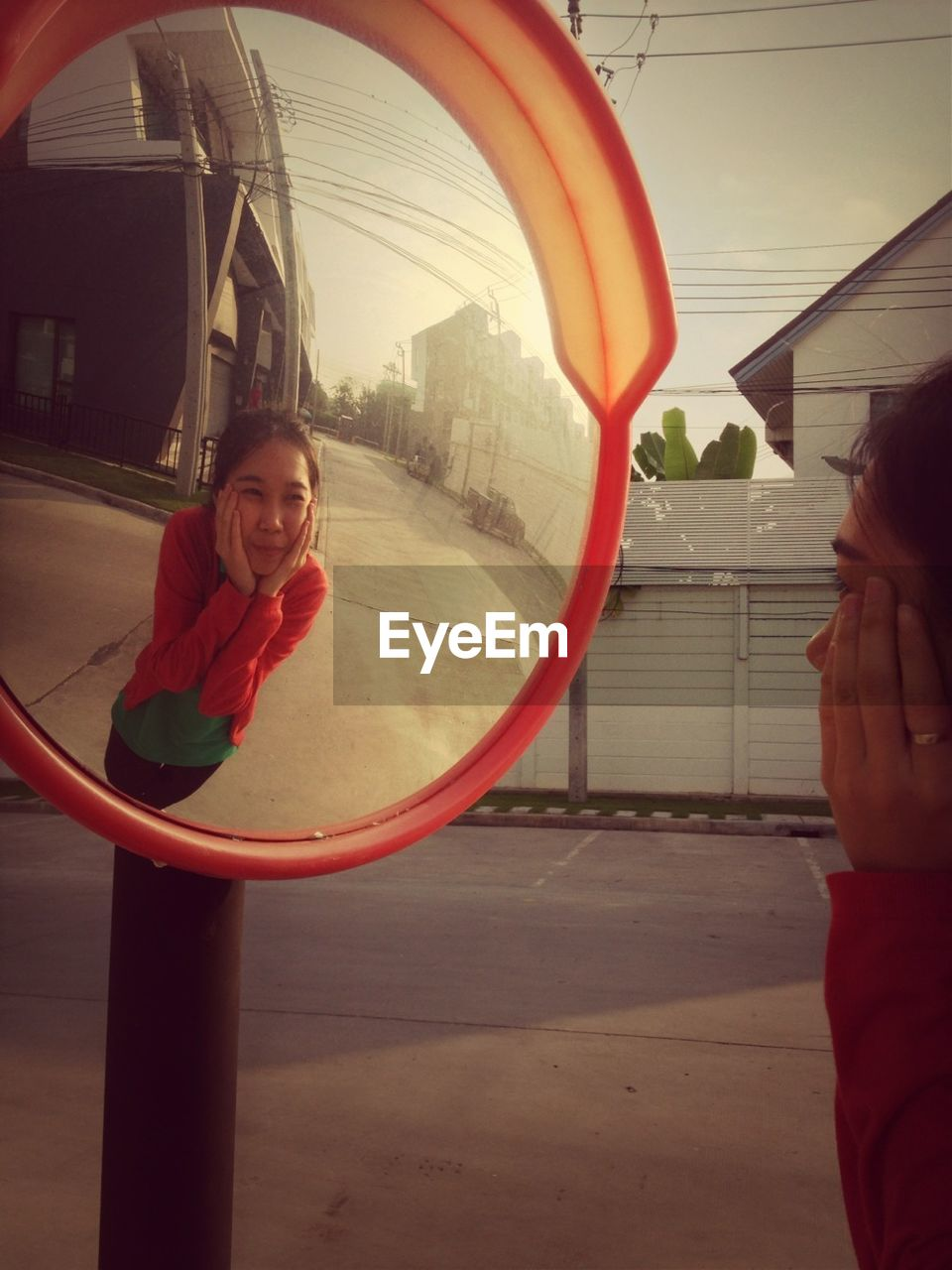 Woman With Hands On Cheeks Reflecting In Road Mirror