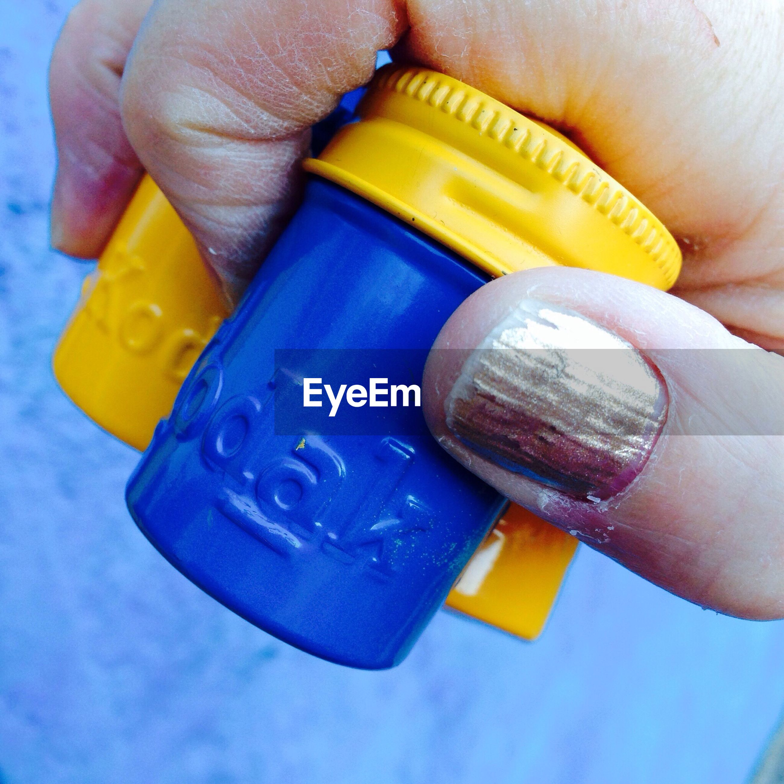 person, part of, holding, blue, cropped, human finger, yellow, multi colored, close-up, unrecognizable person, personal perspective, plastic, nail polish, leisure activity, lifestyles, childhood, indoors