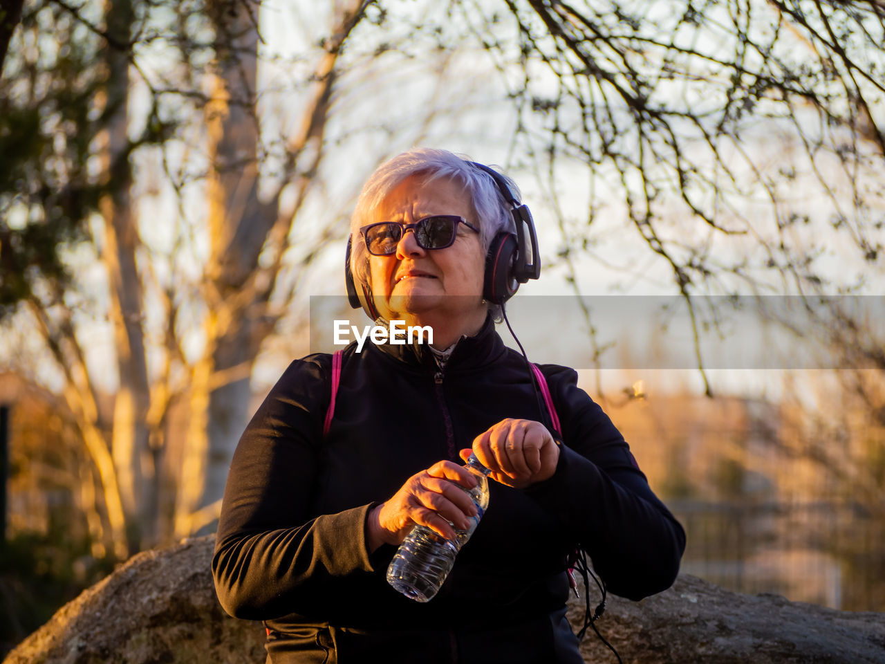 Senior woman listening music in park during sunset