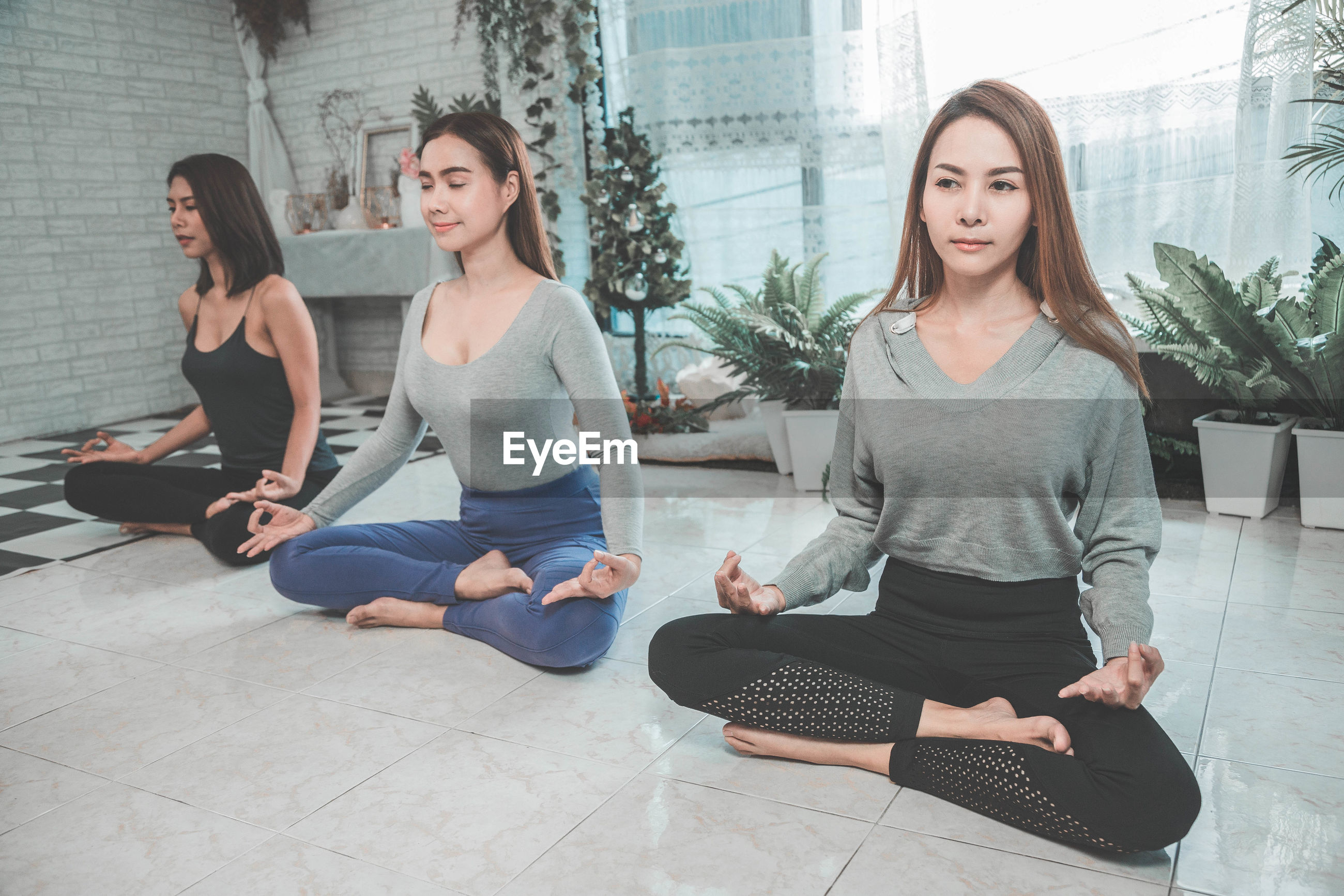 Beautiful women meditating on floor at home