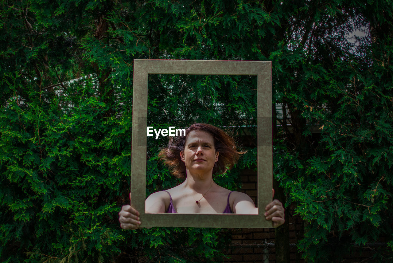 Digital Composite Of Woman Holding Frame Against Trees