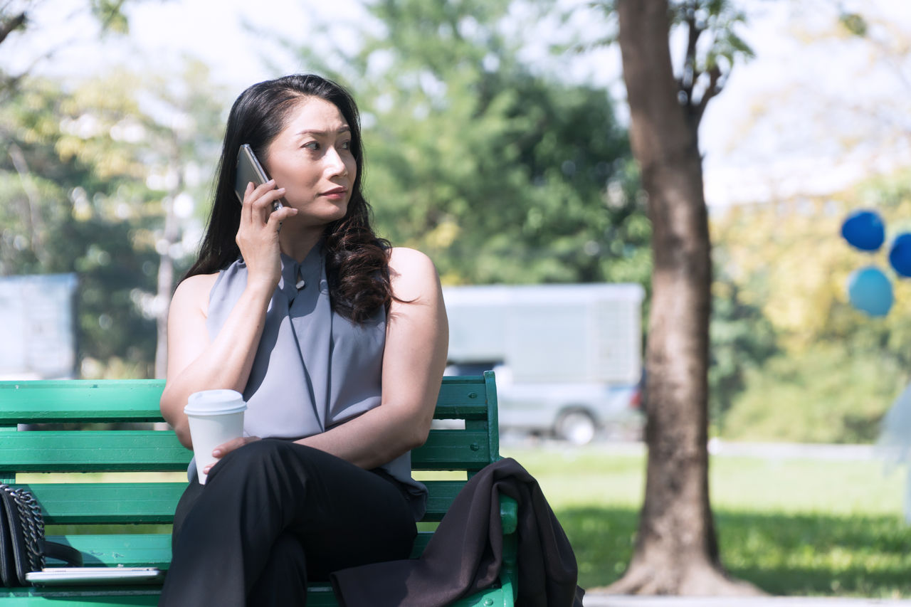 Young woman talking on mobile phone while sitting on bench