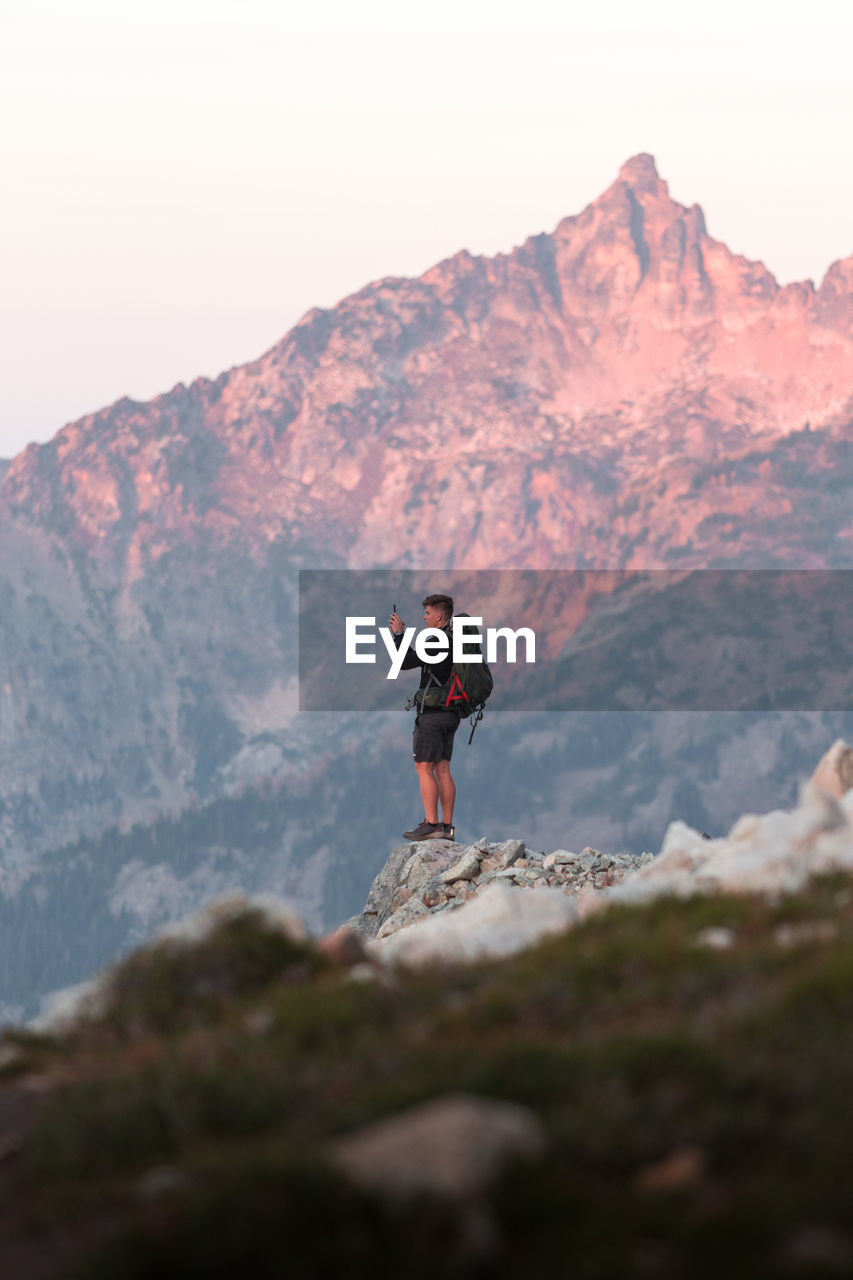 Full length of man standing on rock in mountains against sky