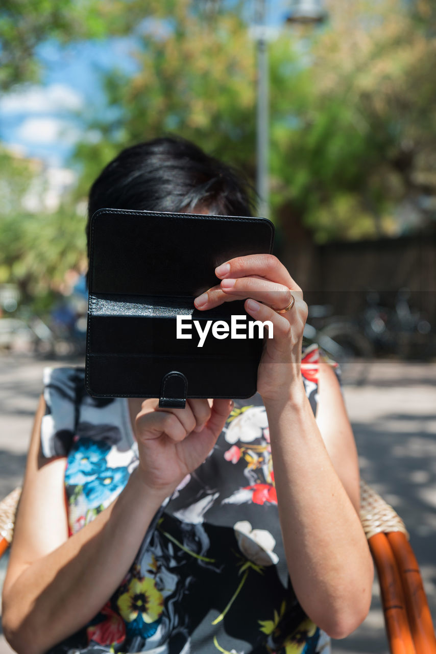 one person, holding, wireless technology, technology, communication, smart phone, activity, mobile phone, photography themes, real people, lifestyles, obscured face, day, leisure activity, photographing, portable information device, connection, telephone, using phone, outdoors