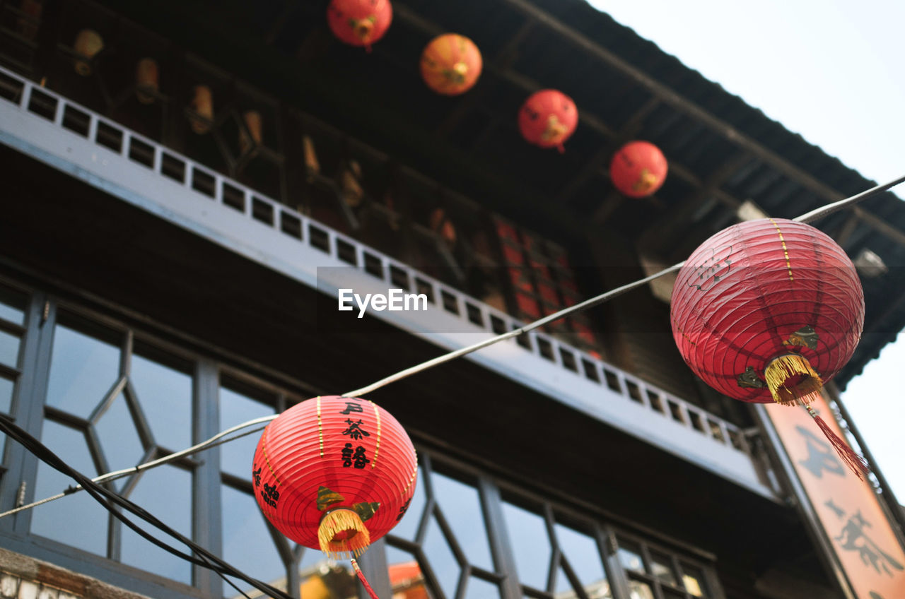 LOW ANGLE VIEW OF ILLUMINATED LANTERNS HANGING ON BUILDING