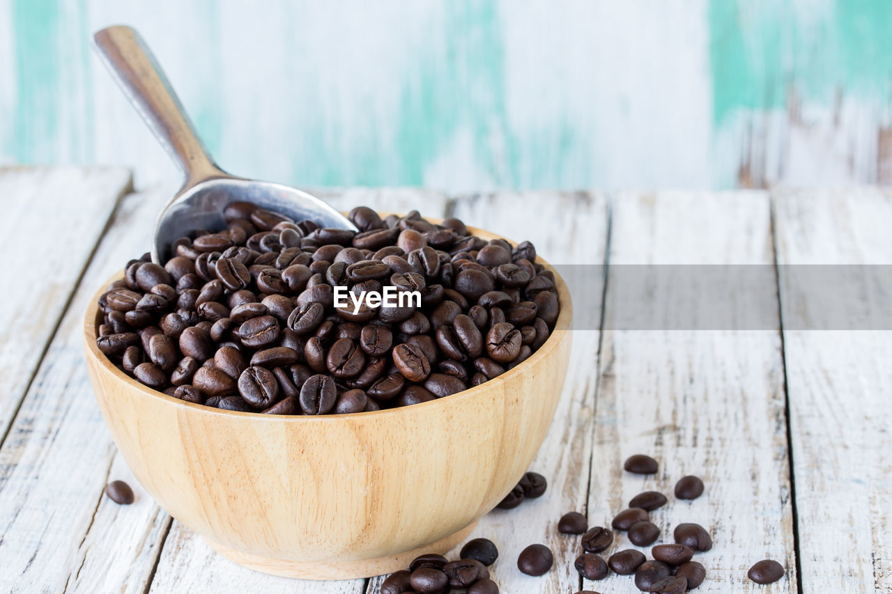 wood - material, roasted coffee bean, brown, still life, coffee, coffee - drink, table, food and drink, large group of objects, indoors, close-up, no people, food, freshness, focus on foreground, spoon, eating utensil, kitchen utensil, abundance, cup, caffeine
