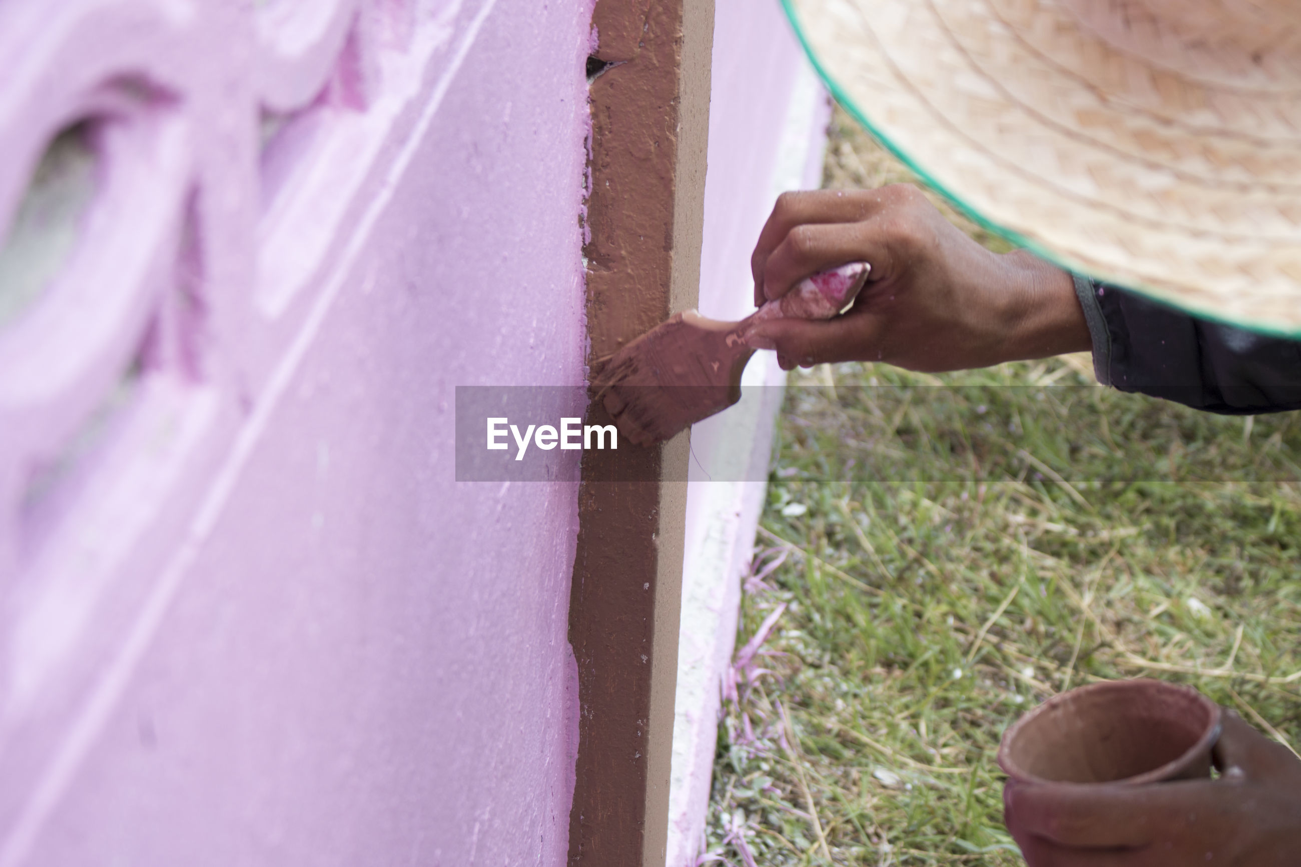 Cropped image of male painter painting brown paint on pink wall