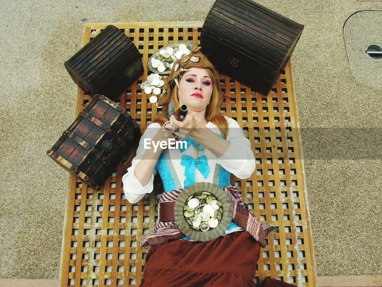 High Angle Portrait Of Female Pirate Pointing Gun While Lying Amidst Treasure Chest