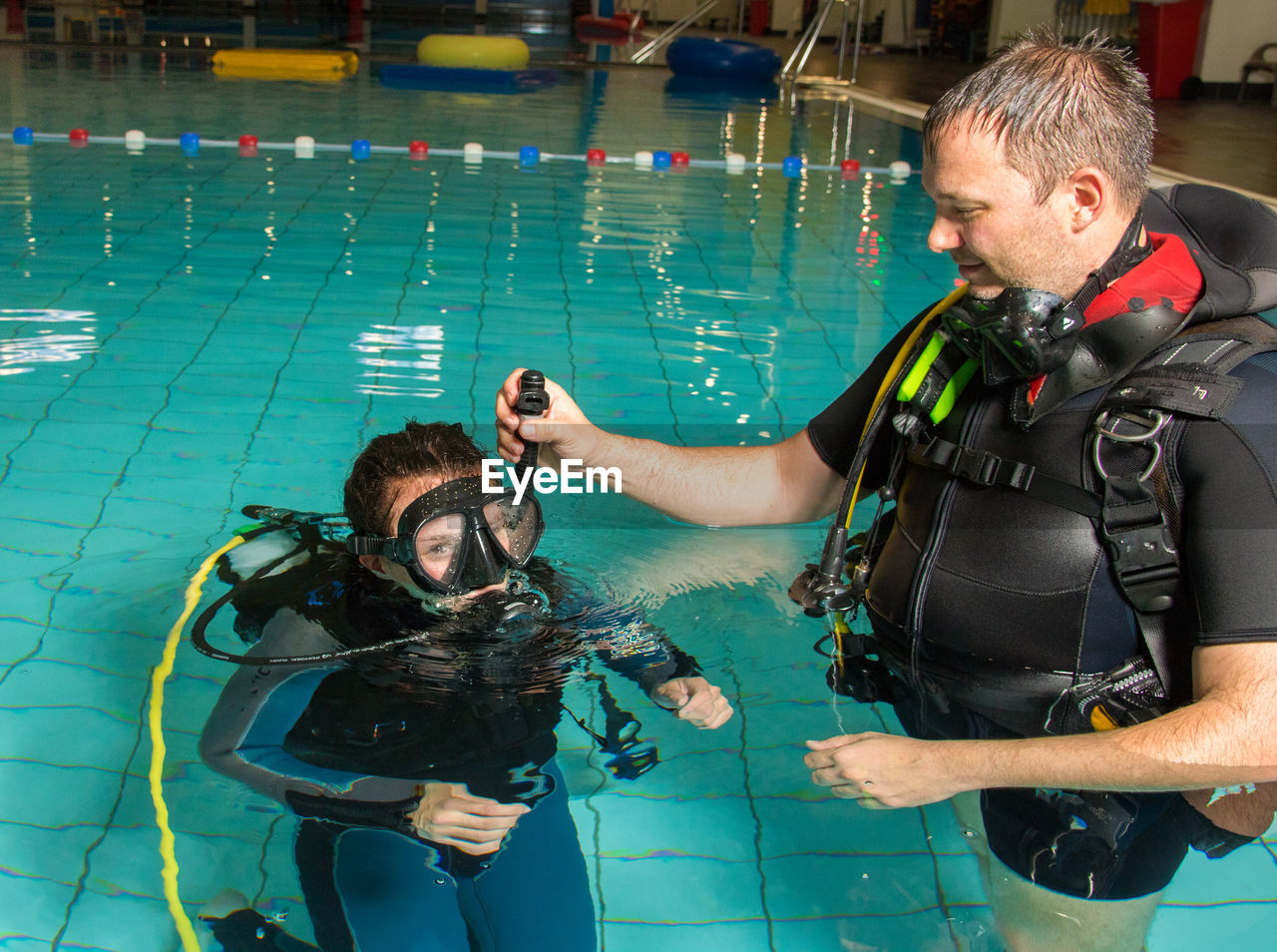 People wearing diving equipment swimming in pool