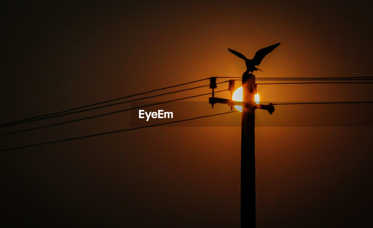 sky, silhouette, sunset, electricity, cable, lighting equipment, orange color, low angle view, technology, sun, no people, power line, nature, fuel and power generation, street light, connection, beauty in nature, illuminated, outdoors, electricity pylon, power supply, light, electrical equipment