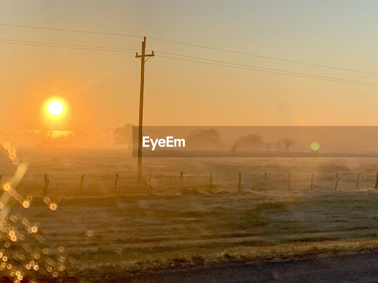 cable, electricity, sky, power line, sun, sunset, field, electricity pylon, environment, land, landscape, tranquility, nature, beauty in nature, no people, tranquil scene, sunlight, technology, scenics - nature, fog, power supply, lens flare, hazy