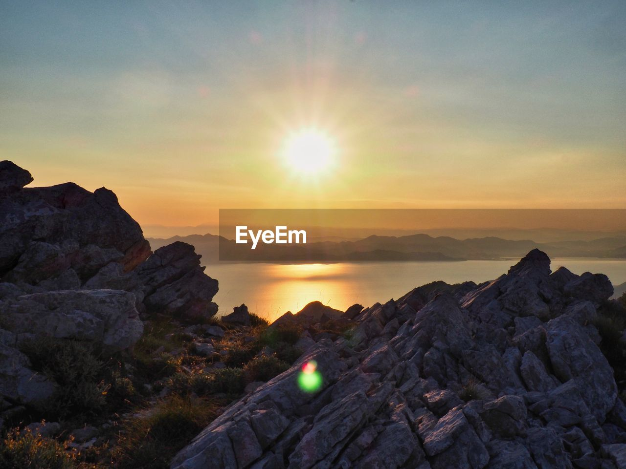 sky, sunset, scenics - nature, rock, beauty in nature, tranquil scene, tranquility, rock - object, sun, solid, nature, non-urban scene, lens flare, idyllic, water, sea, orange color, sunlight, cloud - sky, no people, outdoors, bright