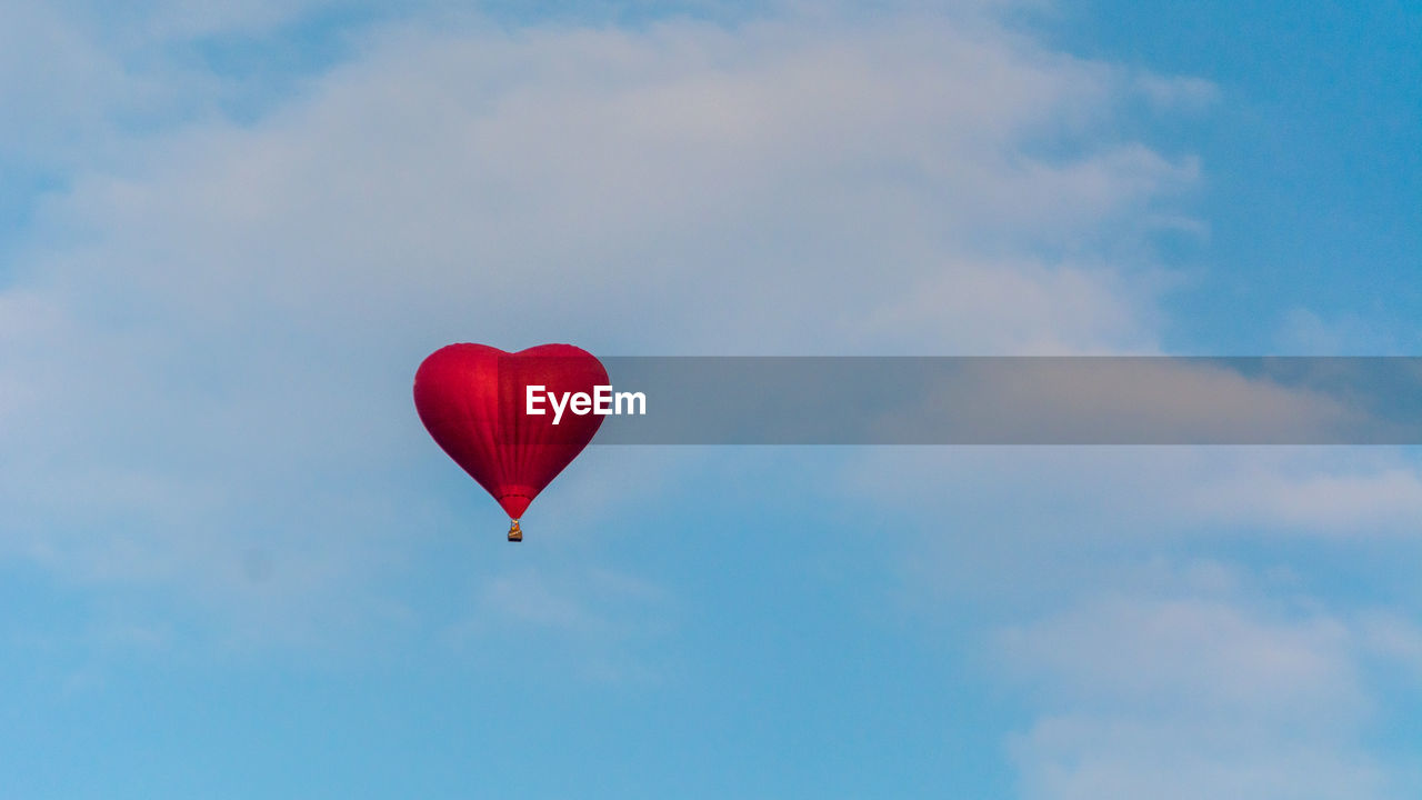 Red Heart Shaped Hot Air Balloon Against Sky