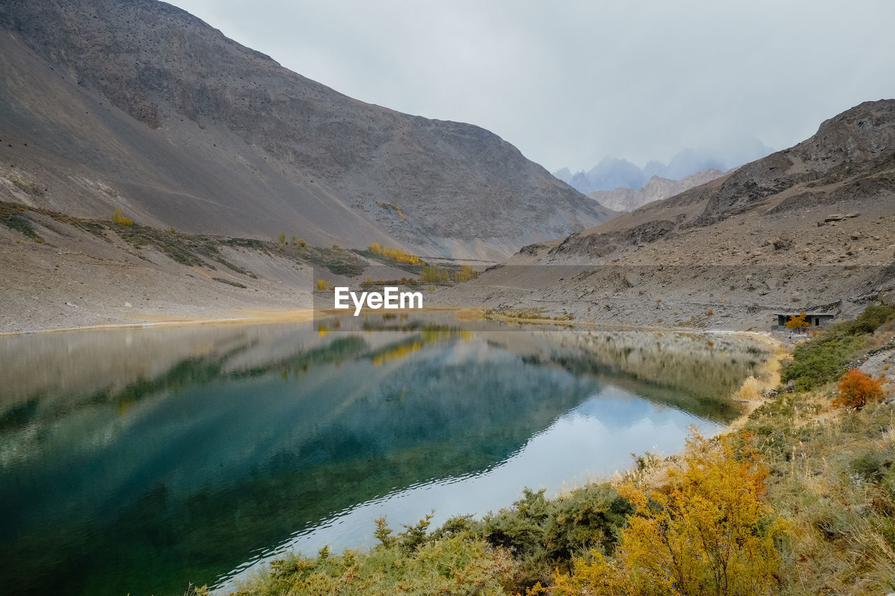 Reflection in water of mountain range at borith lake, gojal hunza valley. gilgit baltistan, pakistan