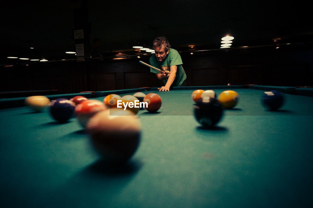 Man Playing Pool At Night