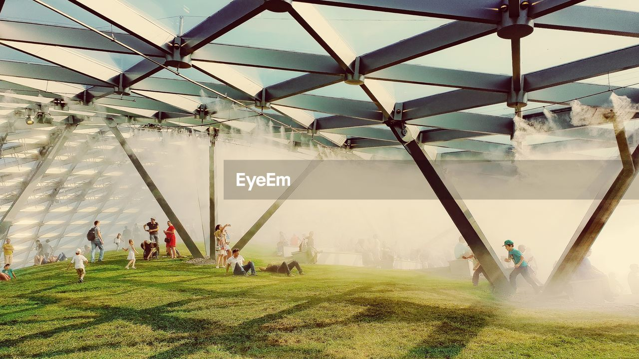group of people, real people, grass, men, crowd, architecture, large group of people, day, leisure activity, built structure, lifestyles, nature, sky, green color, playing, plant, outdoors, women, sport